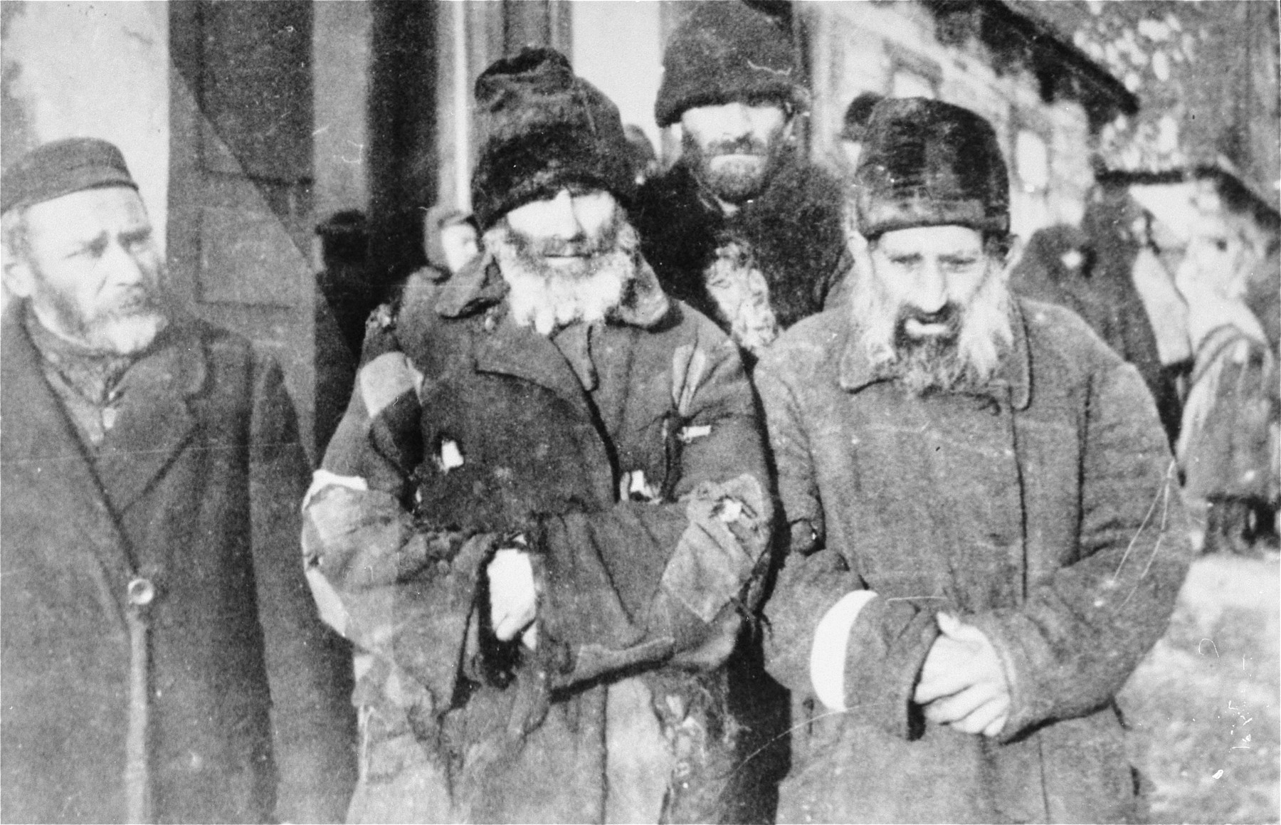 Four Jewish men wearing tattered overcoats pose on a street in the Wisznice ghetto.  Pictured from left to right are: Jankiel Waserman, Wigda Szpektor, Szmul Fojgenbaum and Abram Koltun. They were subsequently deported to Treblinka.