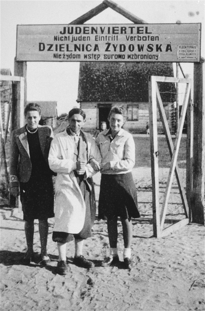 A barber and his two sisters pose at the entrance to the Wisznice ghetto.  The sign above the gate that is written in German and Polish, reads: Jewish quarter, entrance to non-Jews strictly forbidden.  The barber and his sisters were later shot by a German policeman known as Pudel.