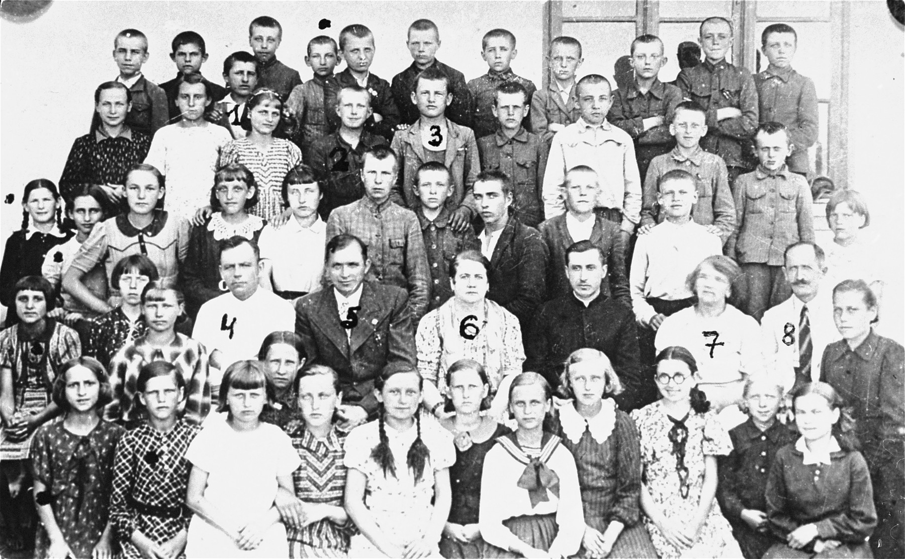 Class portrait of students and teachers at the elementary school in Wisznice.   Children marked with a black dot are Jewish.  The numbered people are 1. Edward Michalczuk (who later did photography in the ghetto for the Germans); 3. Henryk Baranowski; 4. Mr. Krol (music teacher); 5. Mr. Bieszczad (school principal).  One of the children has been identified as Jozef Brodzki.