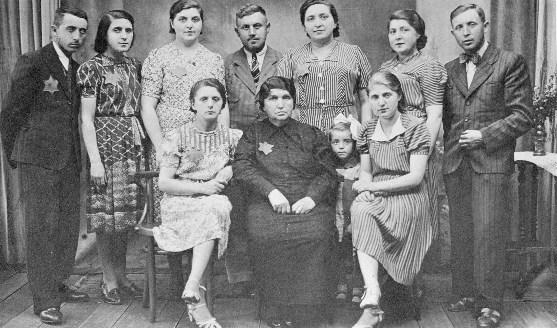 Portrait of the Klein family in the Zelow ghetto wearing Jewish stars.   Standing from left to right: Natan and his wife Rozia, Salka Frant, Hershel, Chana Baila Majer, Tzipa and Abram. Seated are: Bluma, and Lea-Feiga.