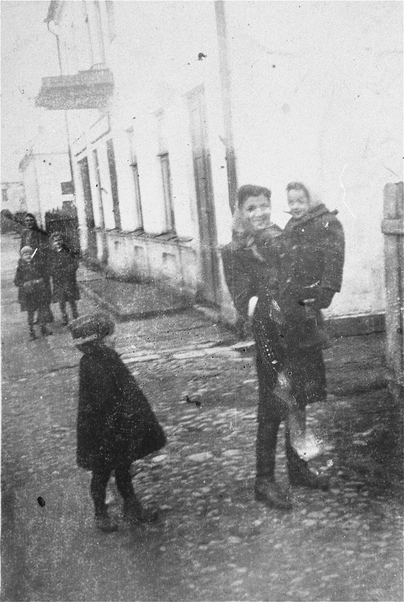 Rachel Ejber holds her niece Sheindel Rajs on a street in the Wlodawa ghetto.  Standing near them is Rachel's cousin Hana Rajs.