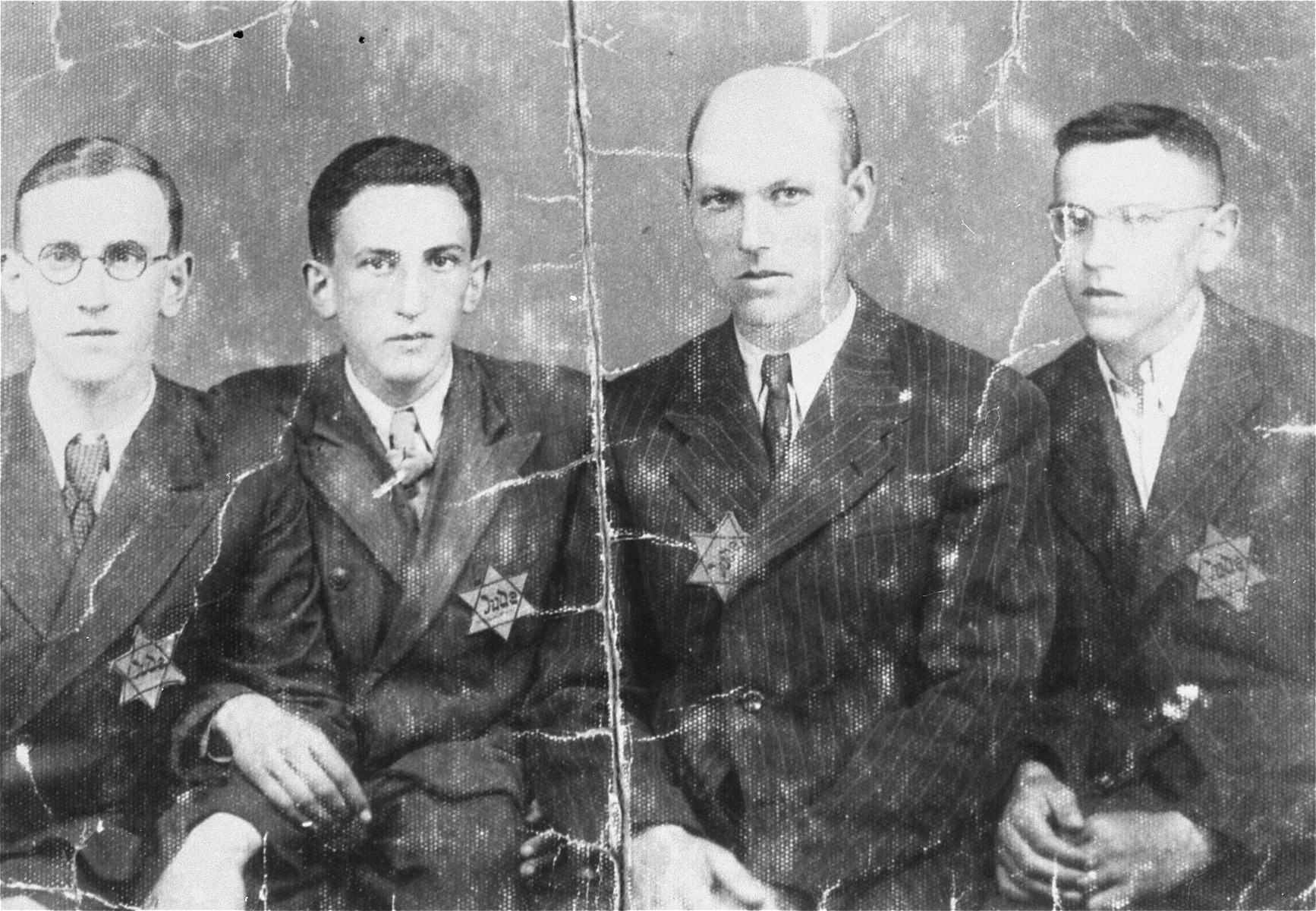 Group portrait of the male members of the Jakubowicz family wearing Jewish badges in the Wielun ghetto.  Pictured are Mr. Jakubowicz (second from the right) with his three sons (left to right), Jakub, Moisze and Henry.  All four survived the war.