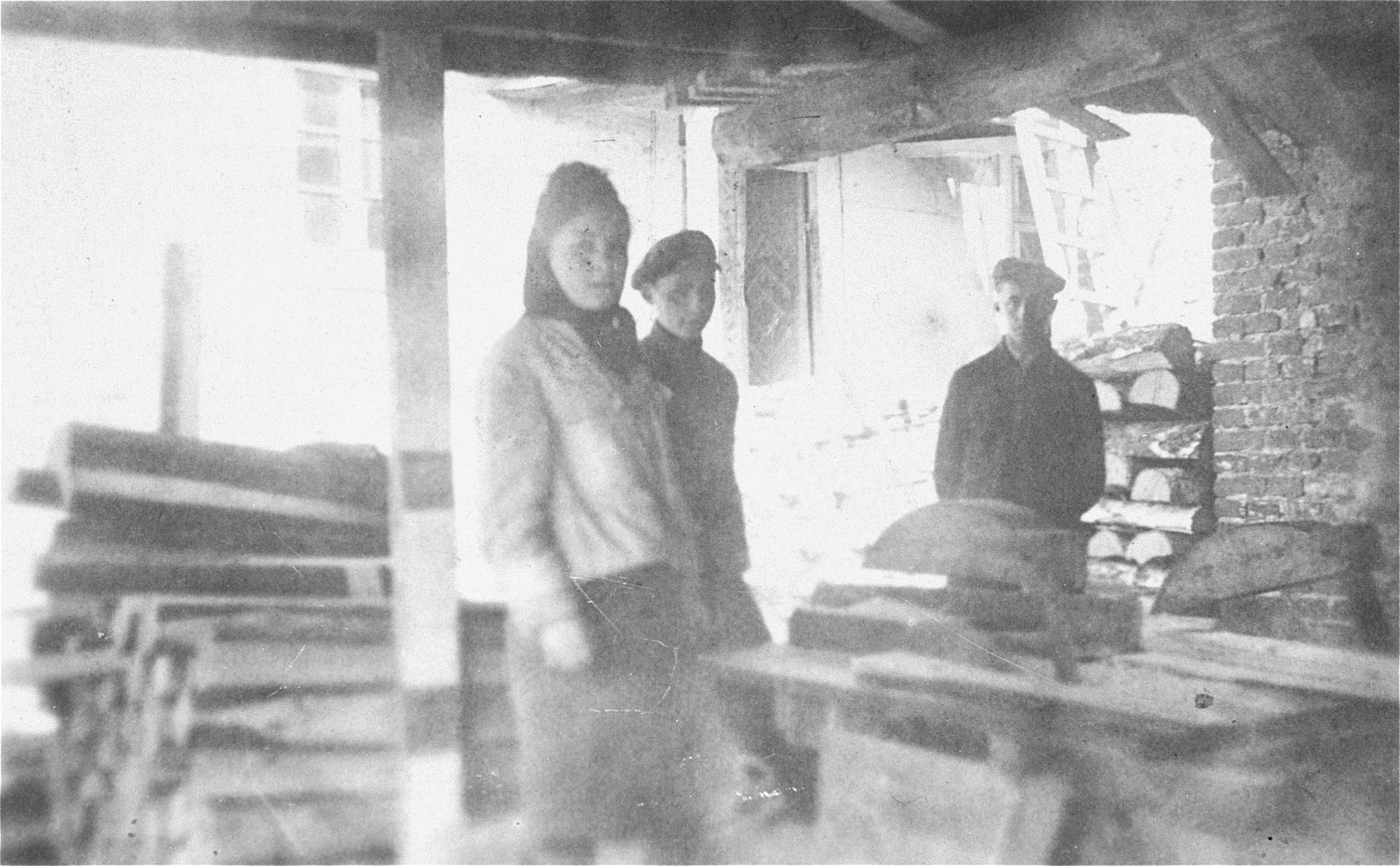 Three young Jews at a sawmill near the Wlodawa ghetto.  Pictured from left to right are Ester Rajs, Isaac Ejber and Jacob Rajs.  Ester perished in Sobibor; Isaac and Jacob were resistance fighters who were killed in Adampol.