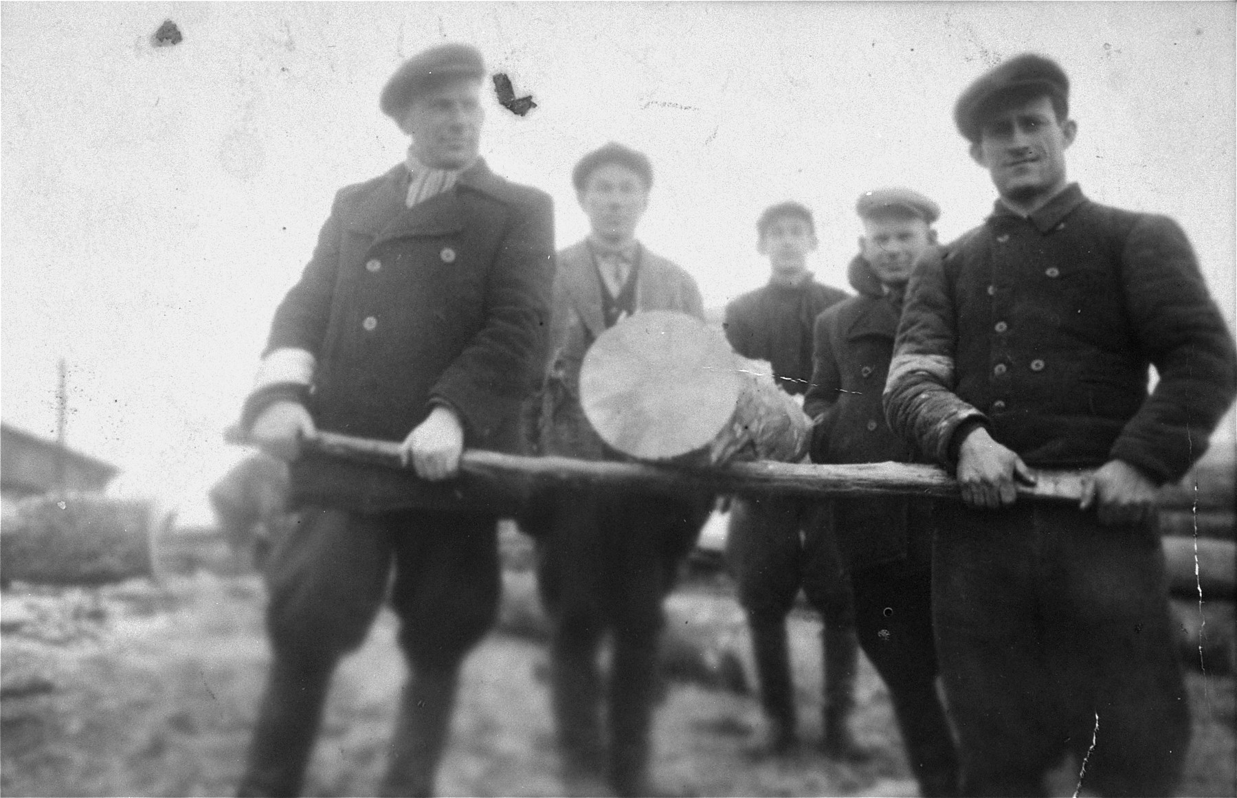 A group of young Jewish men carry a heavy log at a sawmill near the Wlodawa ghetto.  Among those pictured are Gedale Rajs, Isaac Rajs, Isaac Ejber and Jacob Rajs.