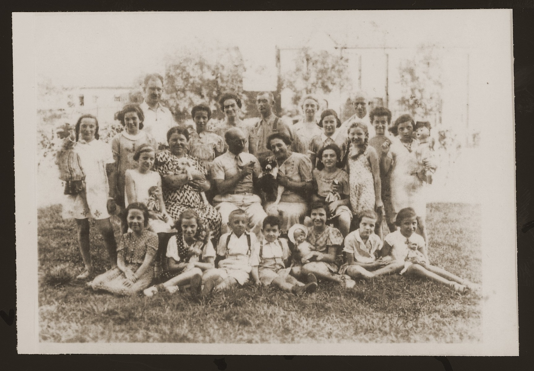 Jewish refugees in the Kinchow refugee camp near Shanghai at the birthday party of Hannelore Mansbacher (now Weill).  Hannelore is seated with her doll on the left in the second row, and Blanka Sender (now Mohtes), is seated with a doll third from right in the second row.  Sender's parents are standing in the last row and Julius and Kaethe Mansbacher, Hannelore's parents, are standing on the right in the back row.  Pictured in the back row, center, is  Rudolf Reif, who was Heimleiter (warden) at the Kinchow refugee camp.