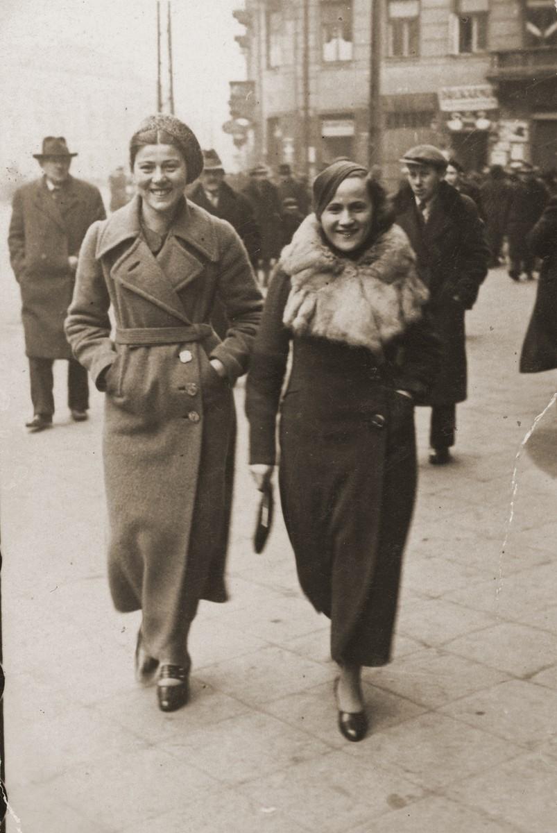 Ita Rozencwajg and her cousin Frieda walk down a street in Warsaw.