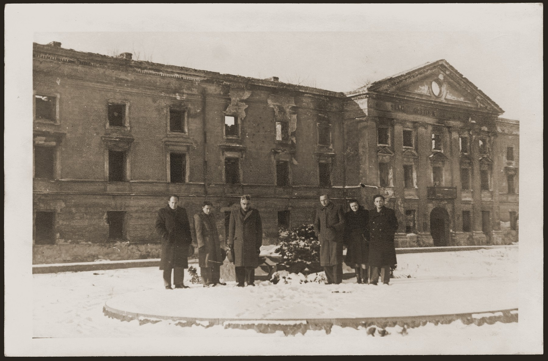 Meir Yaari, head of the MAPAM political party in Palestine, visits the ruins of the Judenrat building in the former Warsaw ghetto.  Yaari is pictured third from the left.  haika Grosman stands second from the right.