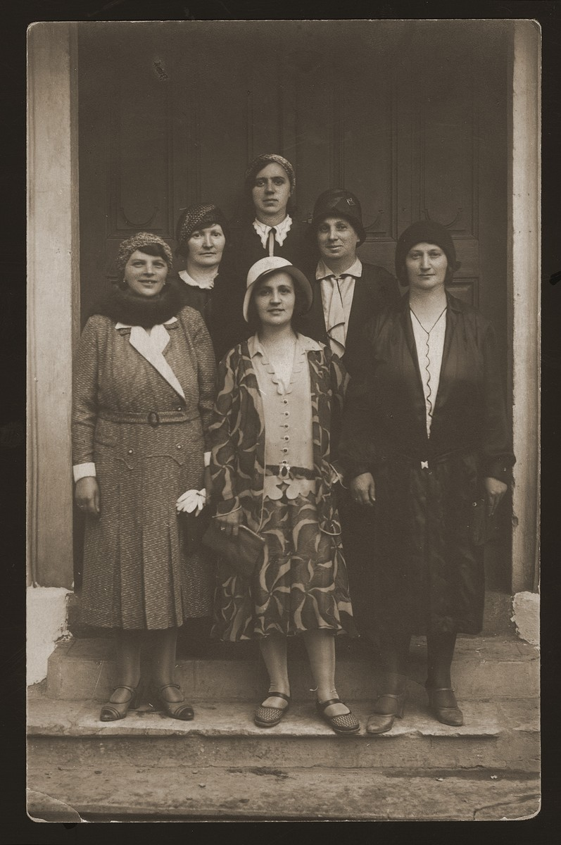 A group of Czech Jewish women pose together in a doorway.    Pictured second from left is Regina Berkovic, wife of the cantor of Senica and in the center is her daughter, Helen Berkovic Goldberger, wife of cantor Eugene Goldberger.