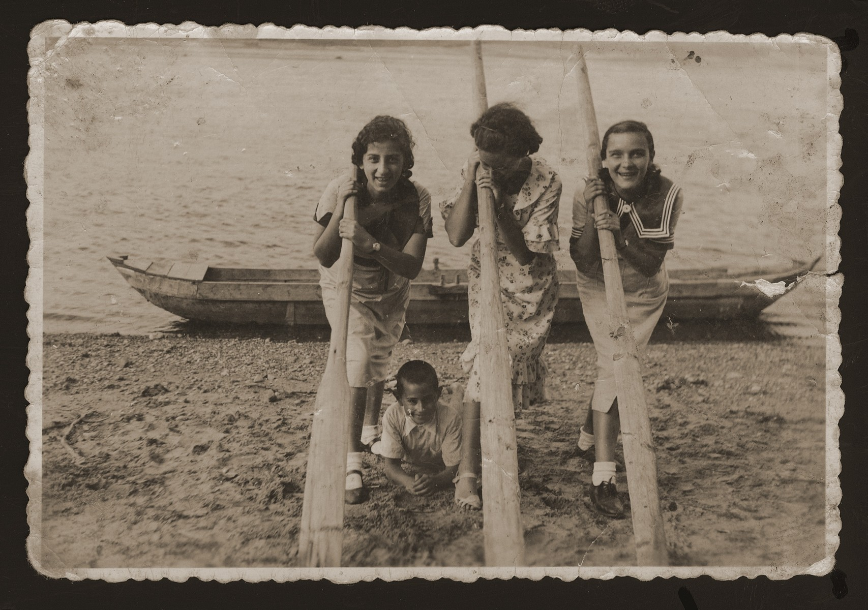 Three Jewish friends pose with paddles on the banks of the Nemunas River in the village of Katcherine near Kaunas.    Pictured from left to right are: unknown, Dita Katz and Celia Rom.  Beneath them is Zvi Katz, Dita's brother.  Neither of Dita's companions survived the war.