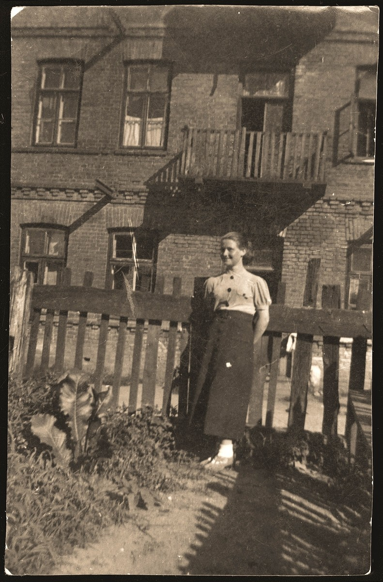 Haika Grosman poses in front of the home of her friend and future husband, Meir Orkin, in Bialystok.  Meir Orkin took this photo on the eve of his departure for Palestine in 1936.