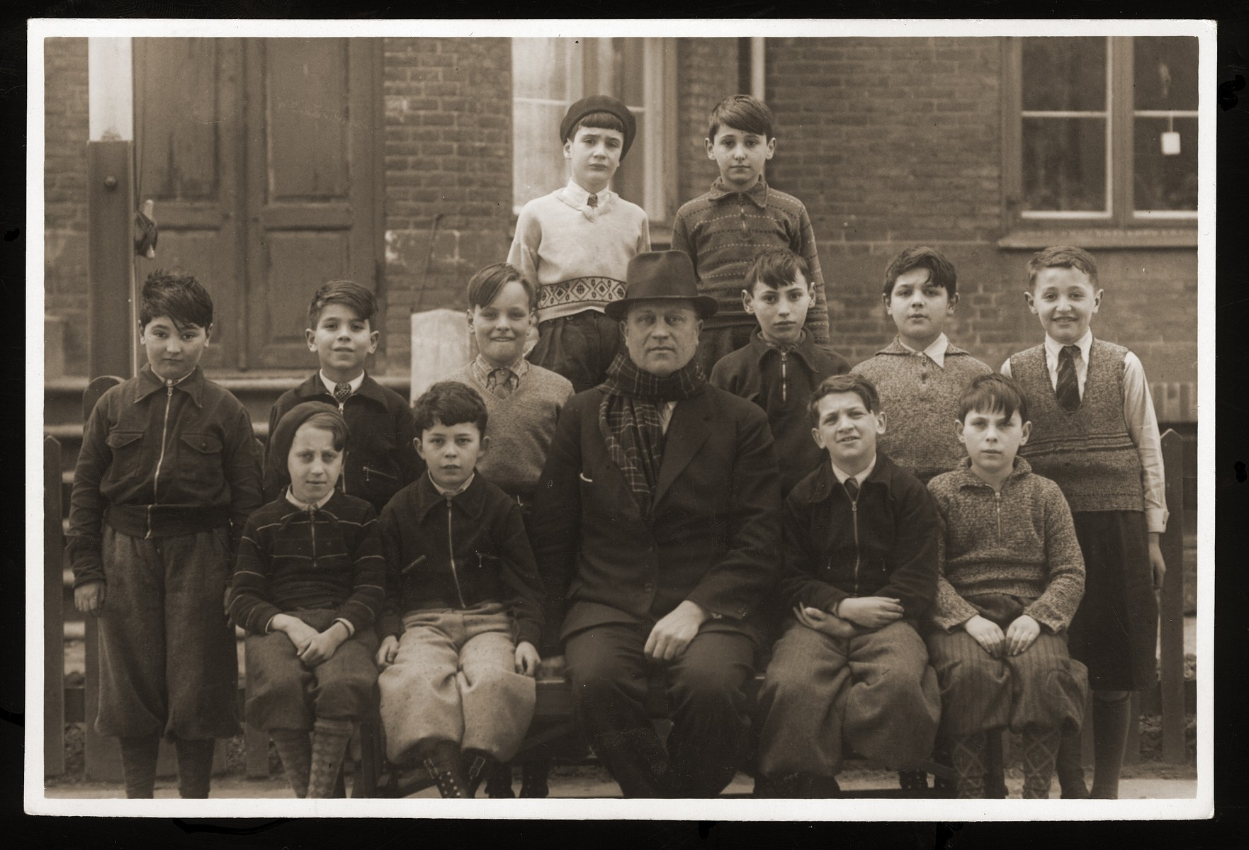 Class of the Mosaik Boys School in Copenhagen.    In the center is the principal, Harry Pihler.  Among the students pictured are front row: Harry Rubin (far left); second row: James Feder (far left), Katznelson (second from left), Skolnik (third from right), Milan Goldberger (far right); third row: Marcus Jakubson (left).   The Mosaik School for Boys and the Caroline School for Girls were established in the beginning of the nineteenth century for the purpose of acculturating the children of Russian Jewish immigrants into Danish culture.  Though most of the teachers were not Jewish, the school also taught Jewish history and religion.