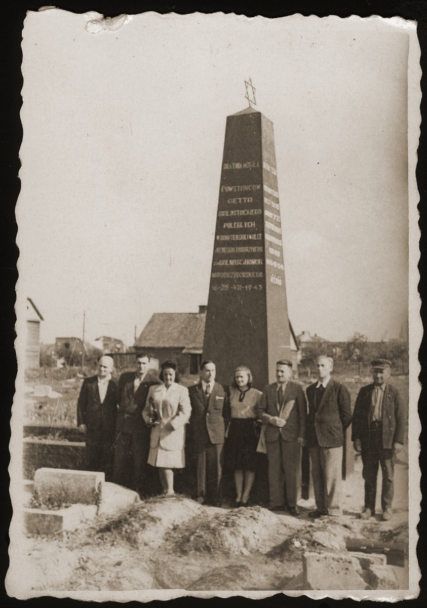 Haika Grosman poses with a group of survivors in front of a memorial to the Jews of Bialystok.