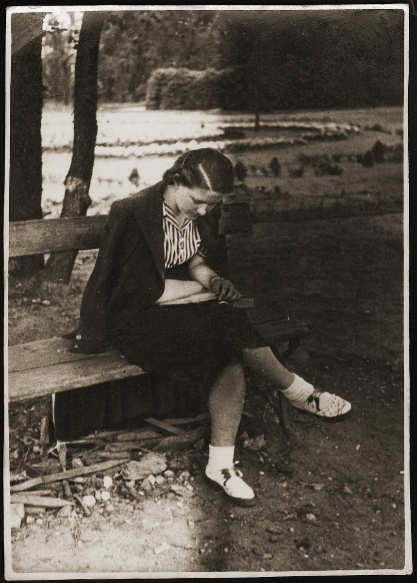 Haika Grosman reads on a park bench in Brest, where she had been sent by the Hashomer Hatzair Zionist youth movement to organize their regional activities.    Grosman sent this photograph to her friend and future husband, Meir Orkin, who had recently immigrated to Palestine.