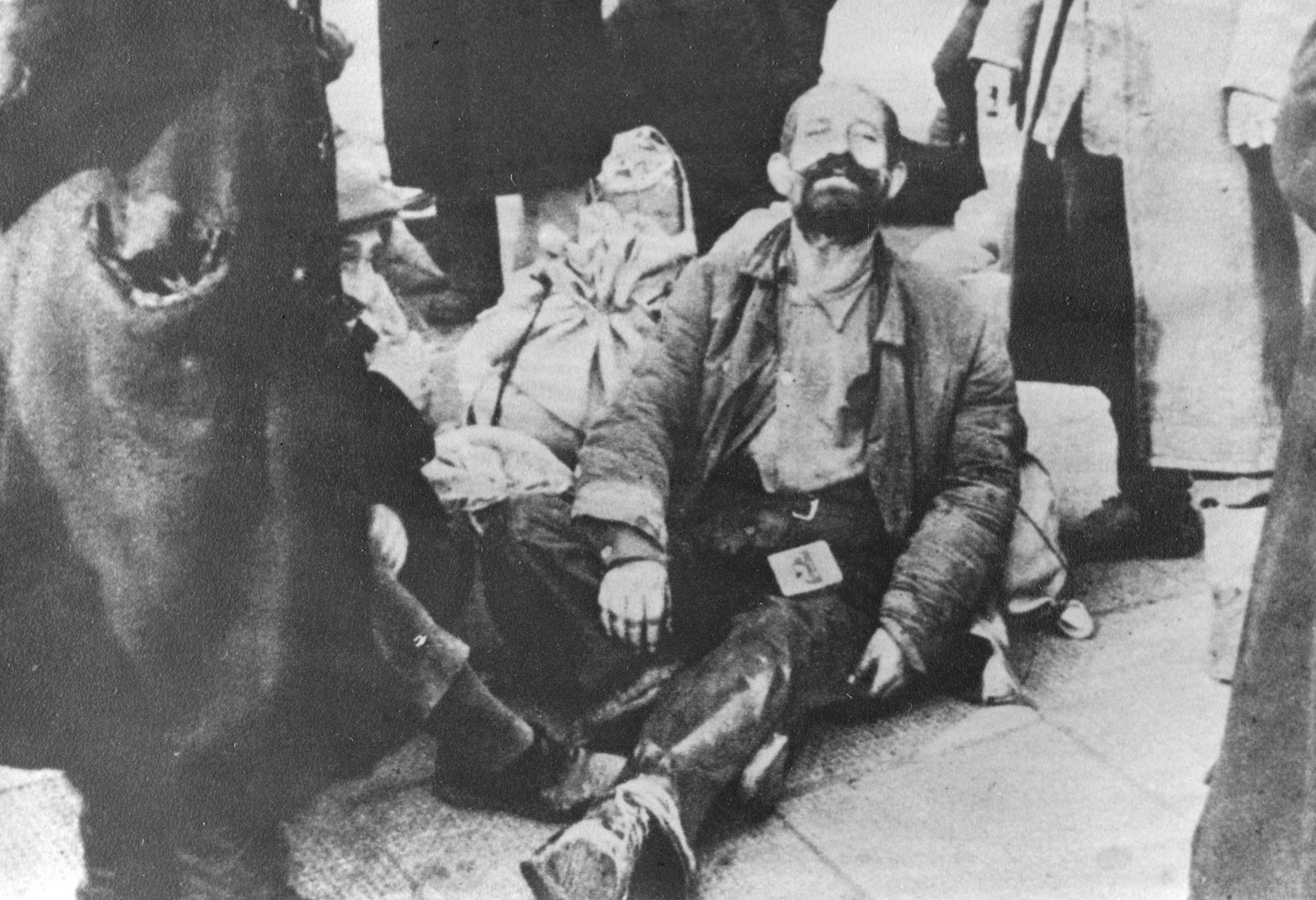 A destitute Jewish man sits on the pavement in an unidentified ghetto in Poland.