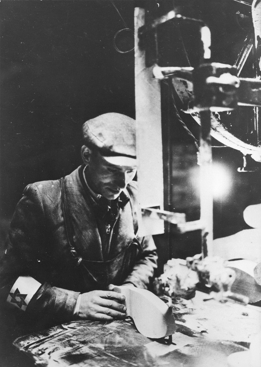 A young man prepares a wooden sole in a shoe-making workshop in the Warsaw ghetto.
