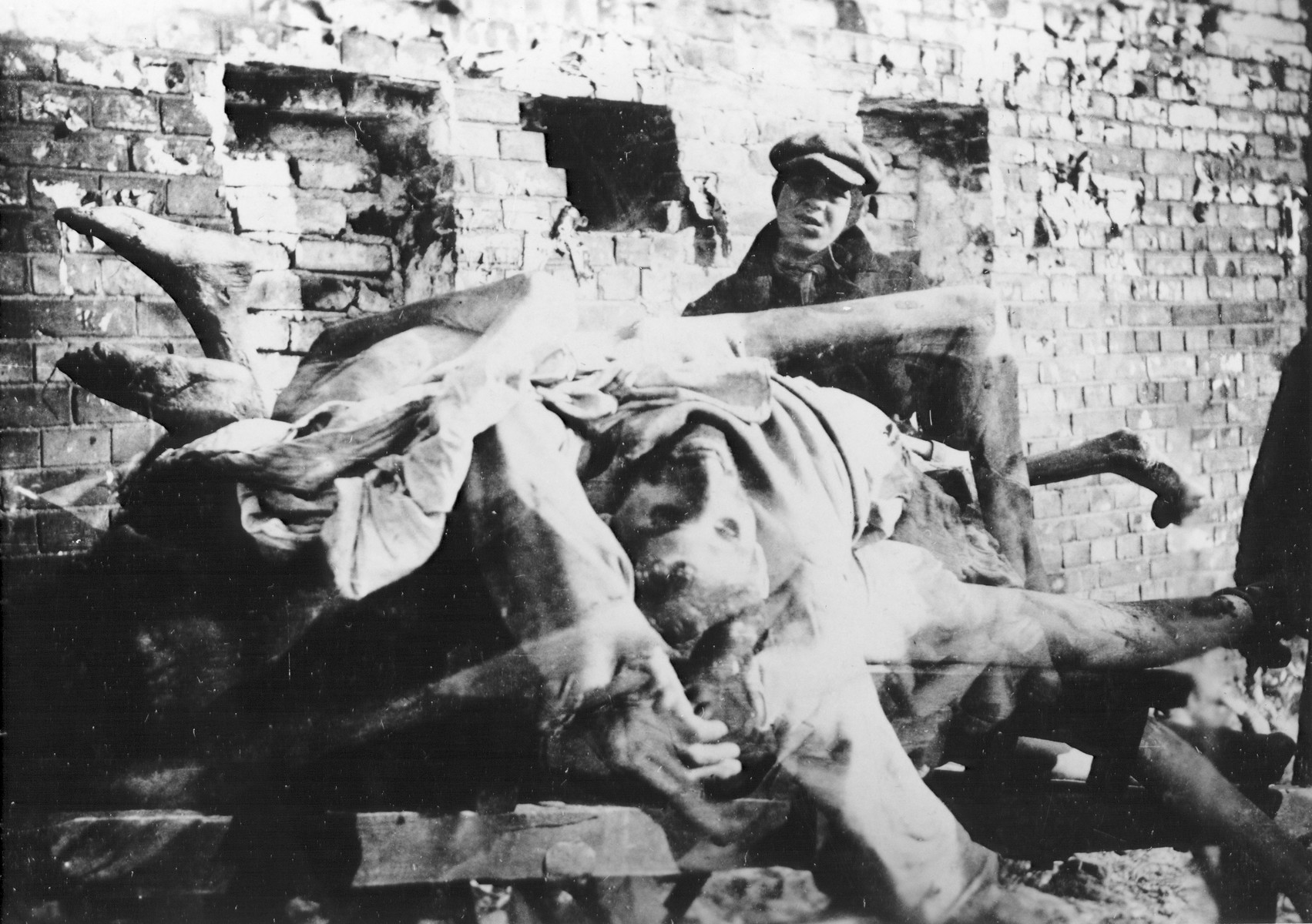 The bodies of Jews who died of hunger and disease in the Warsaw ghetto are stacked up on a cart prior to being removed for burial.