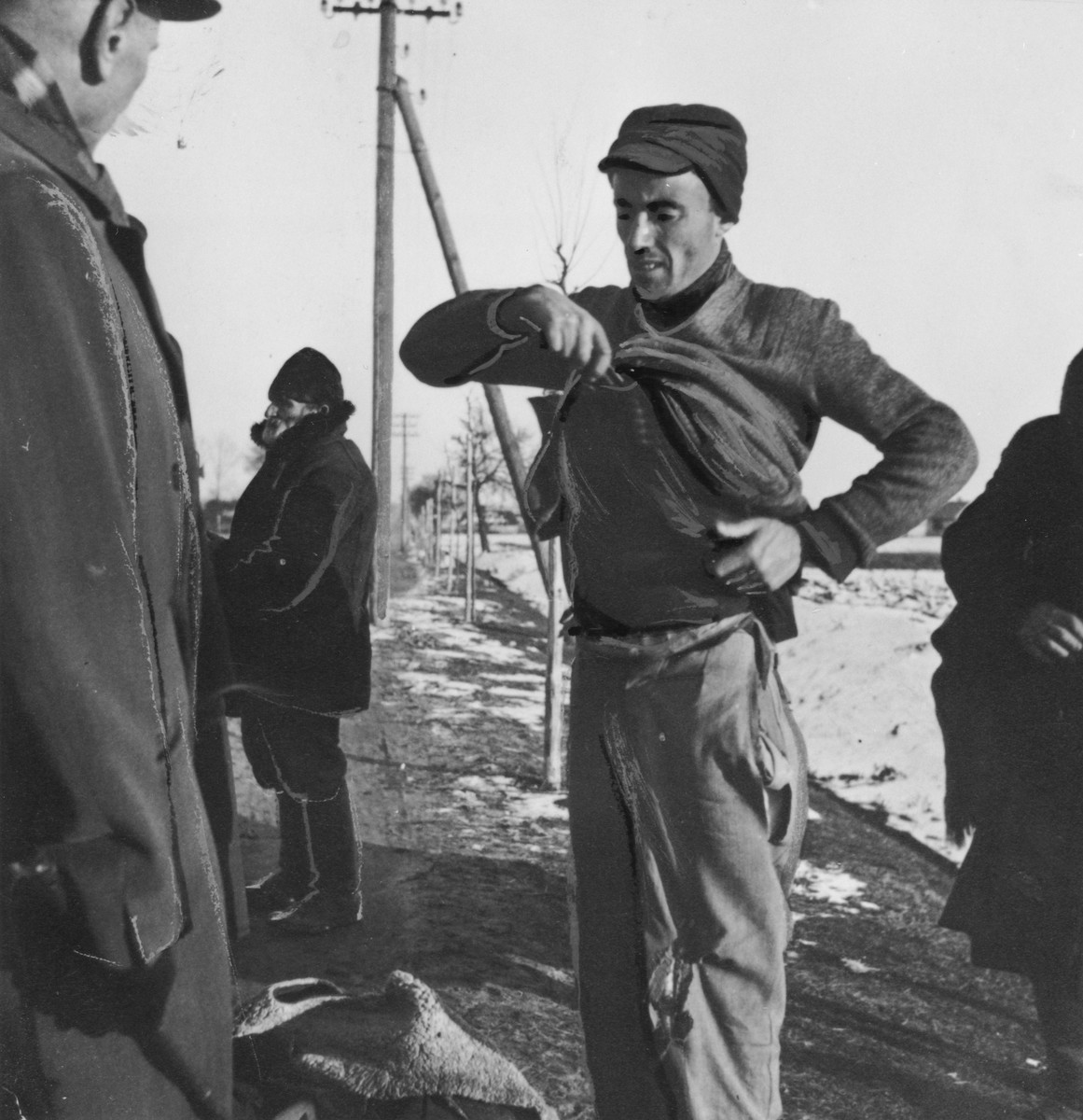 A Jewish laborer from the Radom ghetto is forced to show a German guard what is concealed beneath his sweater.