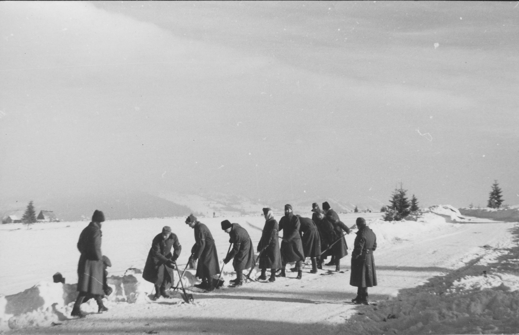 Jewish conscripts in Company 108/57 of the Hungarian Labor Service at forced labor clearing snow from a road.