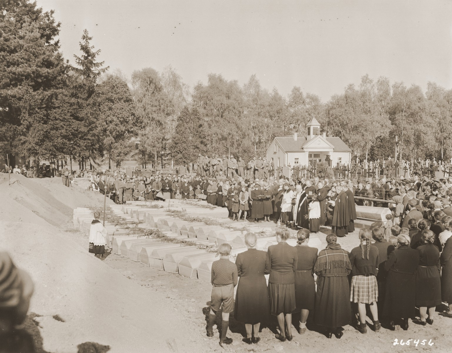 German civilians attend funeral services conducted by the pastor of Schwarzenfeld for the 140 Polish, Russian, and Hungarian Jews exhumed from a mass grave near the town.    The victims died while on an evacuation transport from the Flossenbuerg concentration camp.