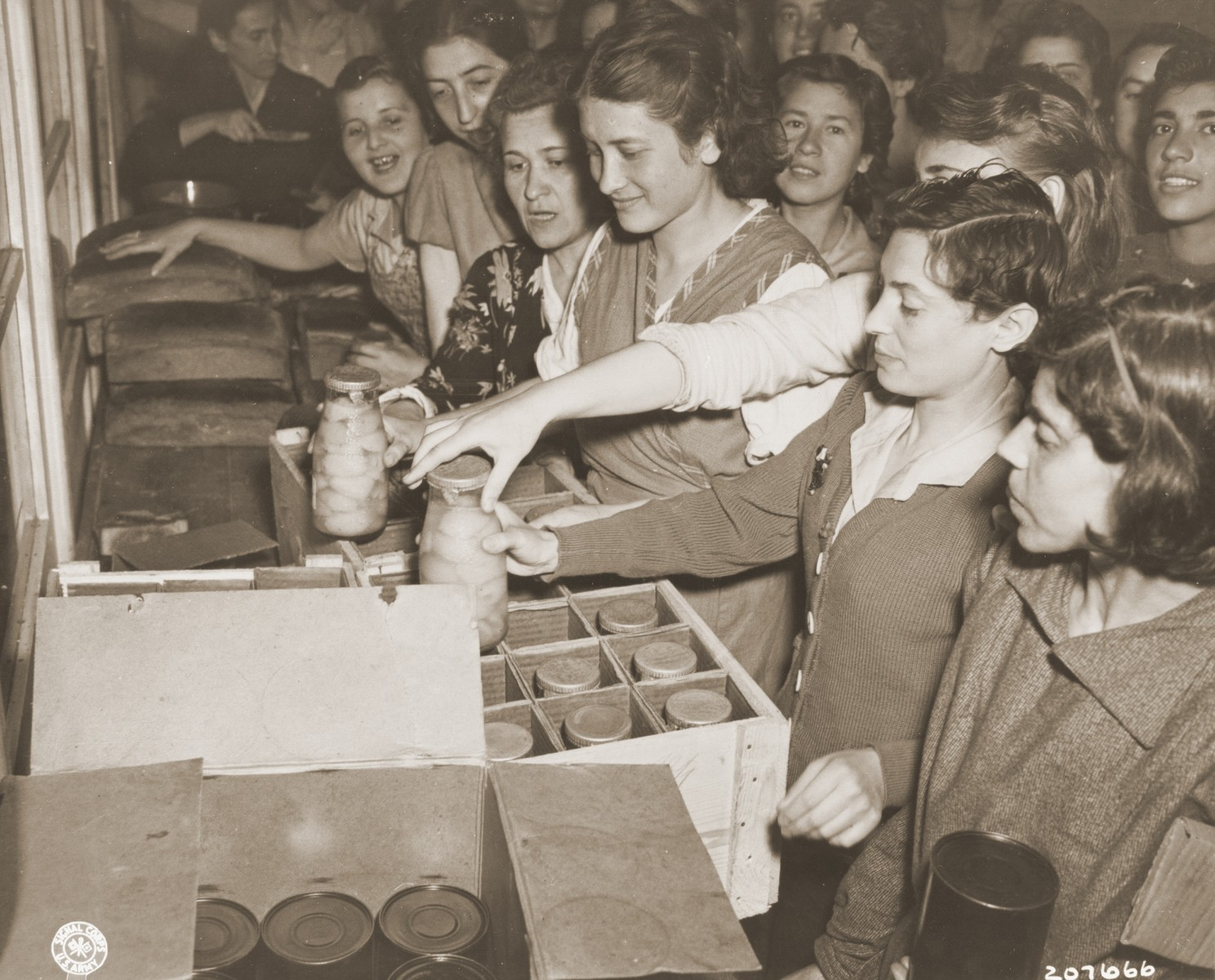 Jewish women liberated from a factory in Mehlteuer are given food seized from Nazi warehouses.    Approximately 400 Jewish women were forced to work in the factory until liberated by the 87th Division of the U.S. Army.  The women had been moved from one city to another, and were previously in Magdeburg before it fell.