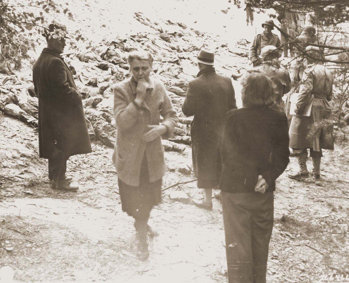 Under the supervision of American soldiers, German civilians look at the bodies of 71 political prisoners exhumed from a mass grave on Wenzelnberg near Solingen-Ohligs.    The victims, most of whom were taken from Luettringhausen prison, were shot and buried by the Gestapo following orders to eliminate all Reich enemies just before the end of the war.
