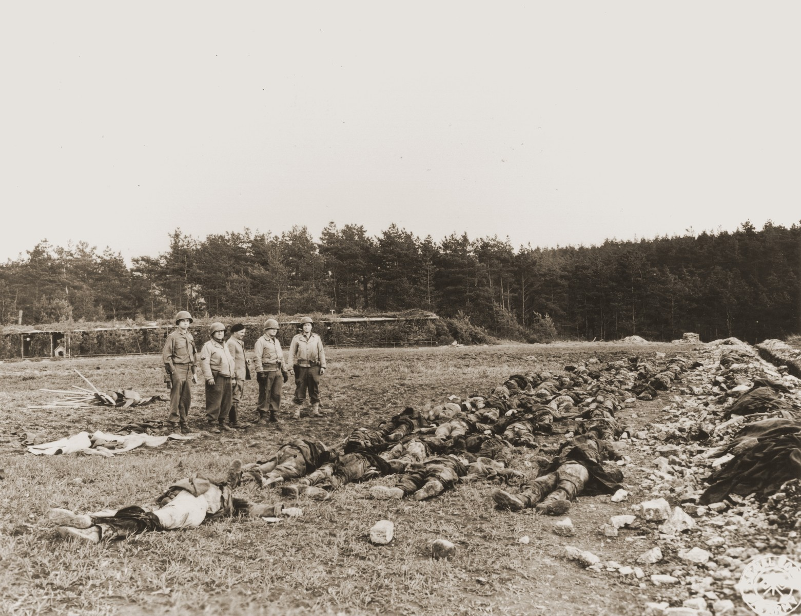 American soldiers view the corpses of slave laborers shot by the SS in the vicinity of Hirzenhain.
