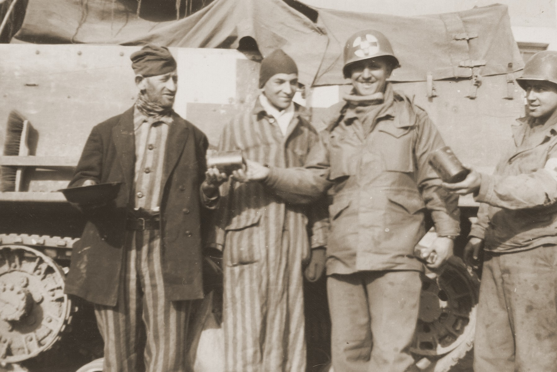 U.S. Army medical personnel with the 10th Armored Division distribute food to two survivors liberated from a concentration camp.    The man in the center is Technical Sergeant George Delmonica.