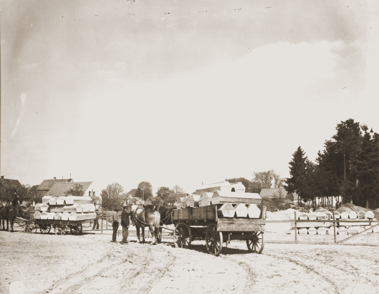 German civilians from Schwarzenfeld transport coffins by wagon to a mass grave near the town from which 140 bodies were exhumed.    The victims died while on an evacuation transport from the Flossenbuerg concentration camp.