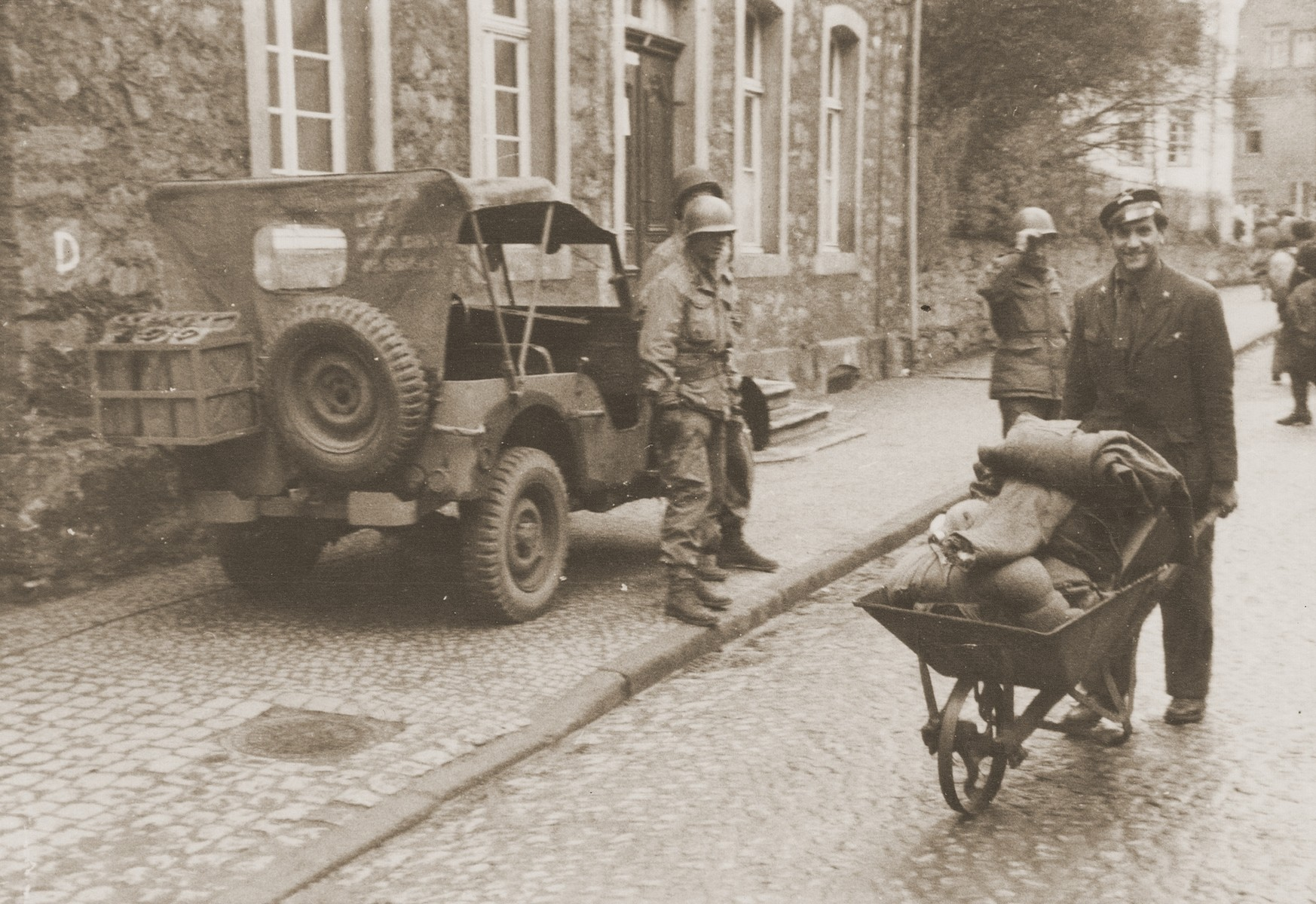 A displaced person carts his belongings through the streets of Dillenburg in a wheelbarrow.