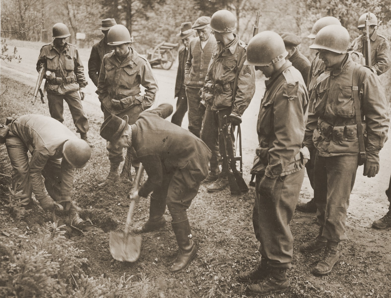 "Members of the 97th Infantry Division, investigating war crimes, force a German civilian to exhume the body of a concentration camp prisoner who was shot by the SS and buried on the side of the road while on a death march from Flossenbuerg concentration camp.  By the beginning of April 1945, Allied forces were closing in on the Flossenbuerg concentration camp, which was situated 20 kilometers NE of Weiden, approximately five kilometers from the Czech border.  Several other concentration camps had already evacuated many of their prisoners to Flossenbuerg earlier in the year, including Buchenwald and Auschwitz, so that by the beginning of May the camp and its satellites were overflowing with almost 52,000 prisoners.  Now, because the area was also about to be liberated, a series of evacuation transports was sent southwest by train in the direction of Dachau.  Allied planes already active in the area had successfully destroyed a number of rail lines and locomotives, effectively delaying many of the transports, or forcing them to take alternate routes.  A number of the trains laden with prisoners were even fired on while in transit, accidentally killing prisoners.  Eventually, most of the prisoners were forced to continue their journey on foot because of the destruction to the German rail system.  During these ""death marches,"" numerous prisoners were killed by the SS for lagging behind or stumbling.  When ammunition ran short after several days of marching, the slower and weaker prisoners were beaten to death rather than shot.  Some of the bodies were buried by prisoners who were kept at the back of the group for exactly this purpose.  Others were just left on the side of the road."