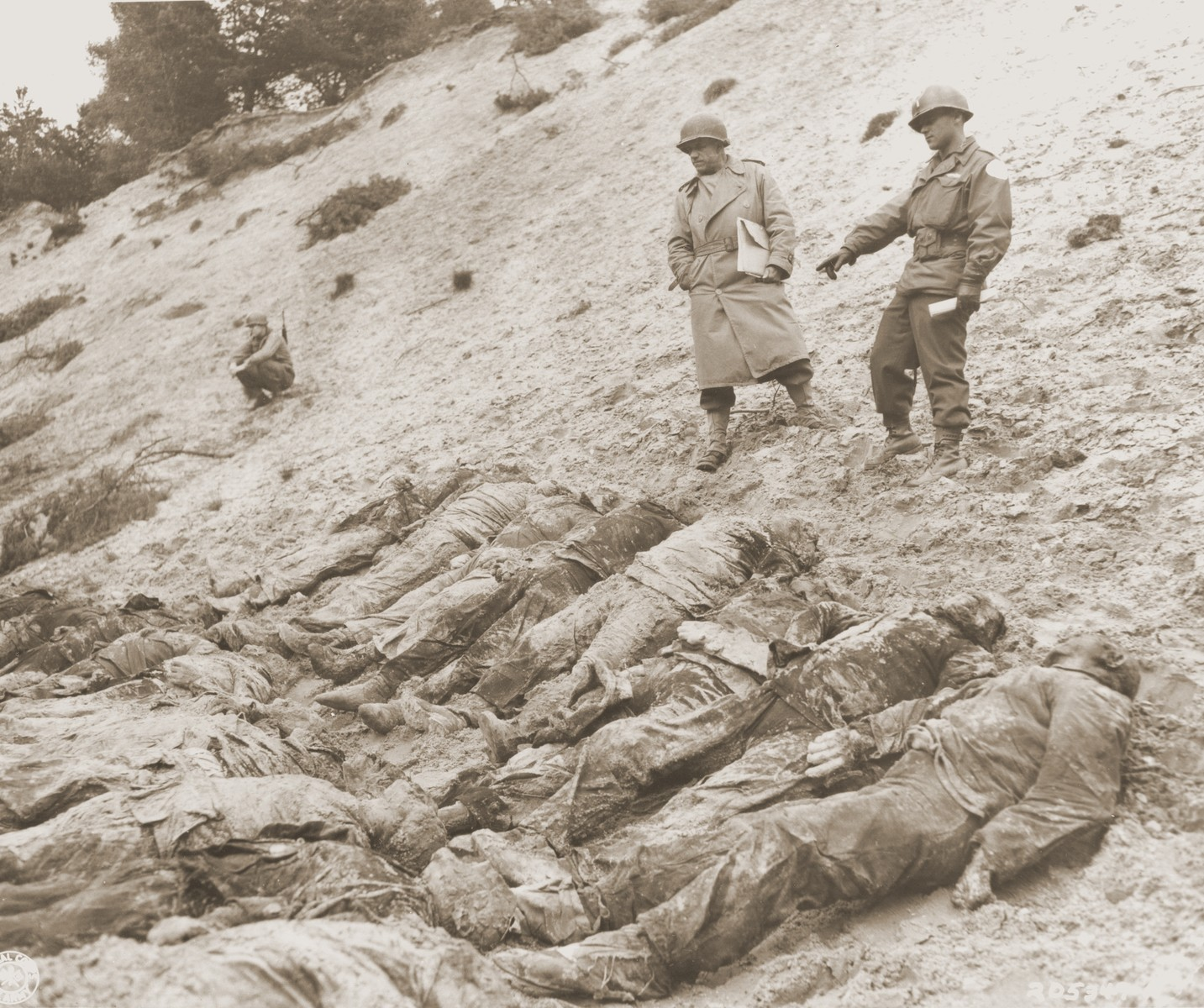 Lt. Col. A. H. Smith (left) of the War Crimes Branch, Judge Advocate General Department, and Lt. Walter Szelaga examine the bodies of 71 political prisoners exhumed from a mass grave on Wenzelnberg near Solingen-Ohligs.    The victims, most of whom were taken from Luettringhausen prison, were shot and buried by the Gestapo following orders to eliminate all Reich enemies just before the end of the war.