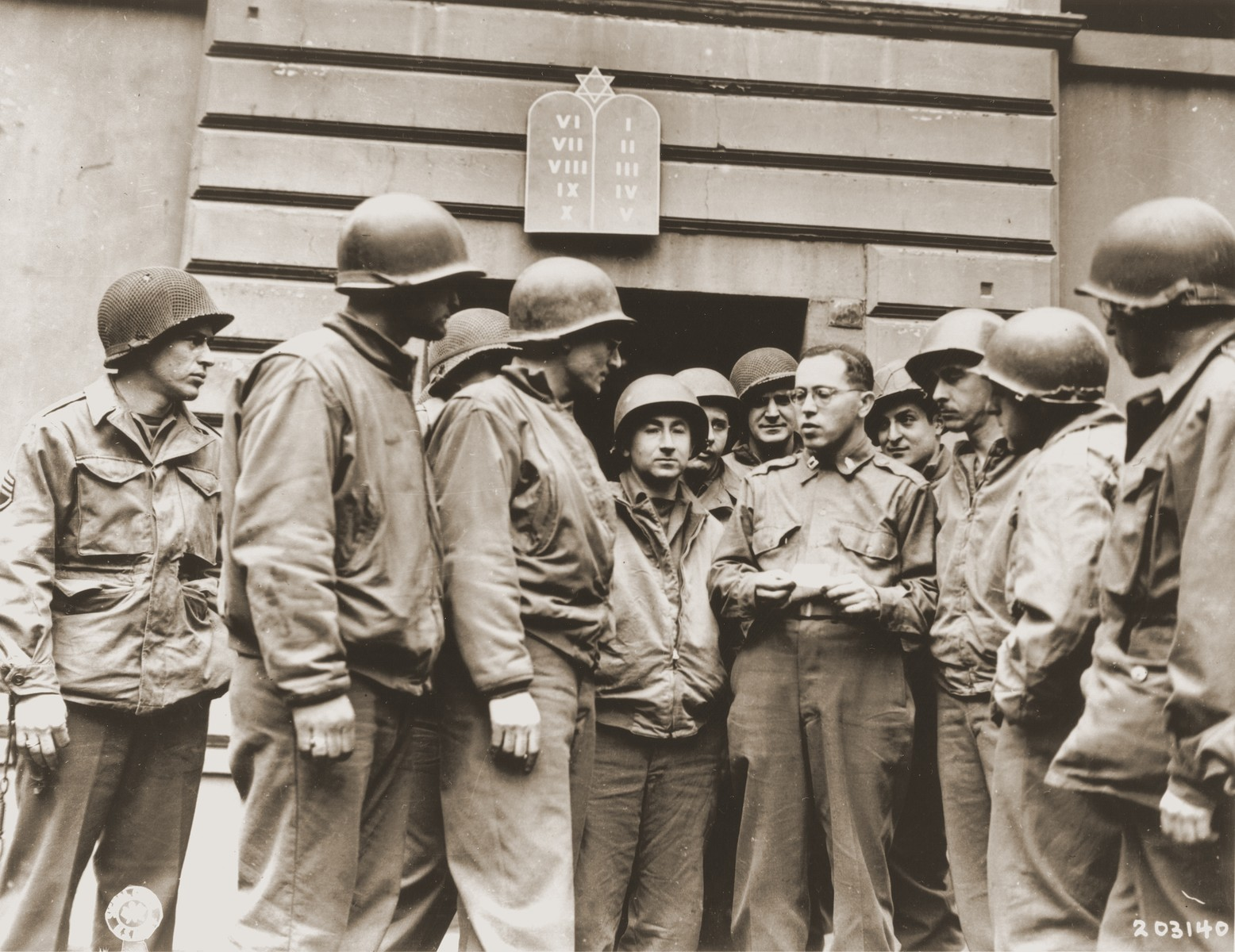 American Army chaplain Rabbi Samuel Blinder converses with a group of Jewish soldiers outside a synagogue in Germany.