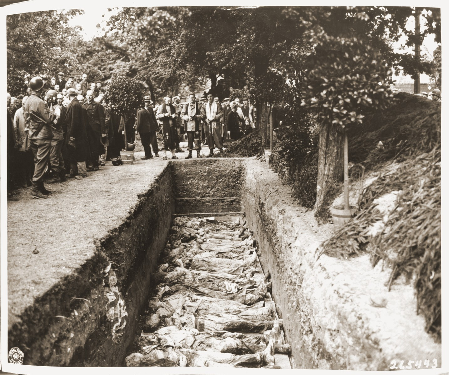 Protestant, Catholic and Jewish chaplains conduct funeral services for the reburial of 71 political prisoners, exhumed from a mass grave near Solingen-Ohligs, in front of the city hall.    The victims, most of whom were taken from Luettringhausen prison, were shot and buried by the Gestapo following orders to eliminate all Reich enemies just before the end of the war.