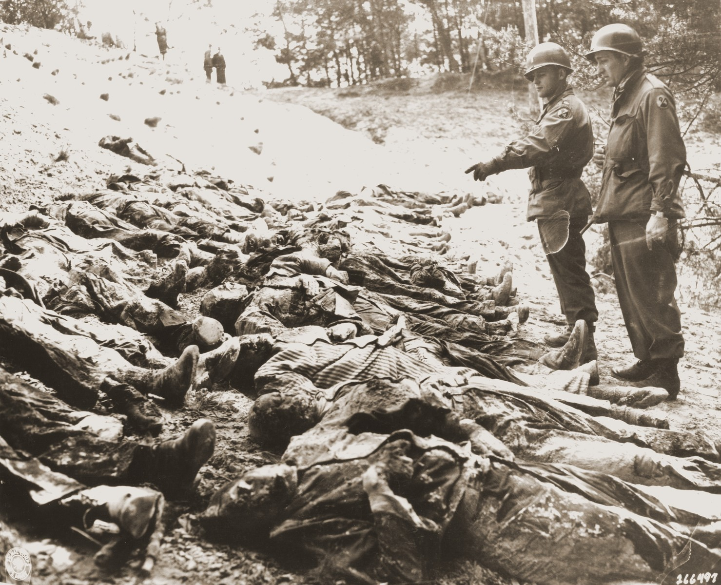 Two American officers with the 94th Division count the bodies of 71 political prisoners exhumed from a mass grave on Wenzelnberg near Solingen-Ohligs.  The victims, most of whom were taken from Luettringhausen prison, were shot and buried by the Gestapo following orders to eliminate all Reich enemies just before the end of the war.