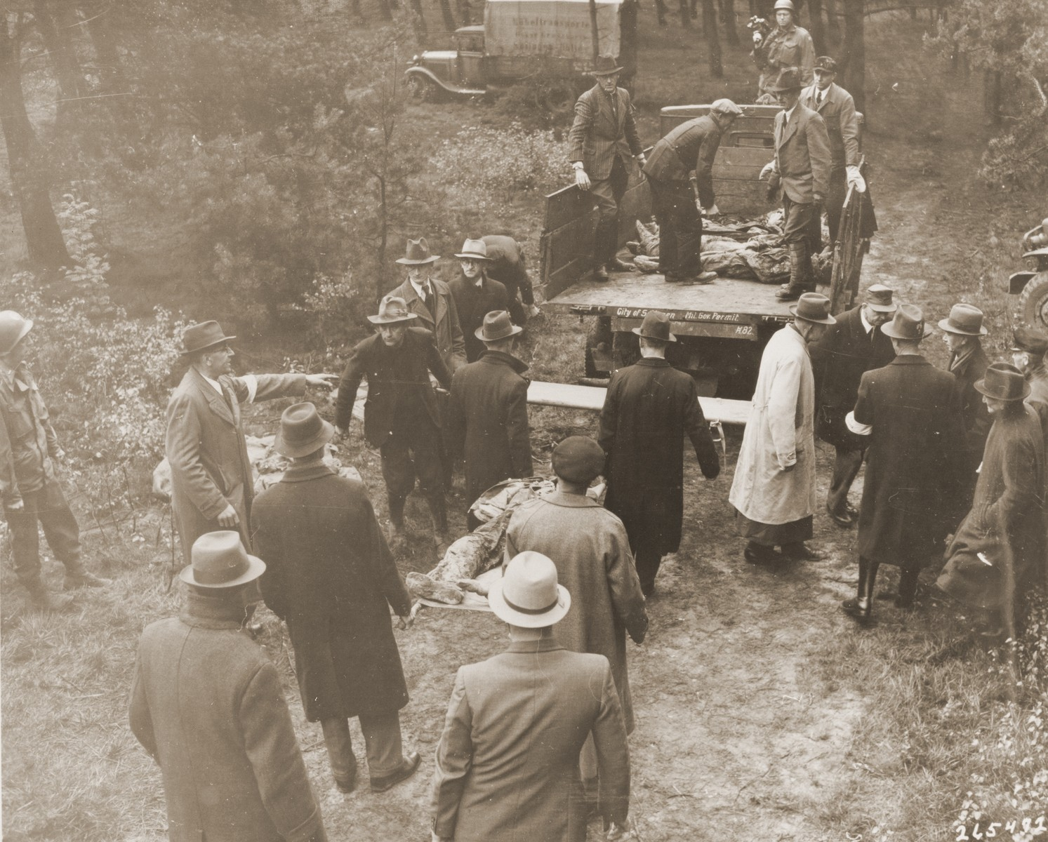 Under the direction of American soldiers, German civilians transport the bodies of 71 political prisoners exhumed from a mass grave on Wenzelnberg near Solingen-Ohligs to the town for reburial.    The victims, most of whom were taken from Luettringhausen prison, were shot and buried by the Gestapo following orders to eliminate all Reich enemies just before the end of the war.