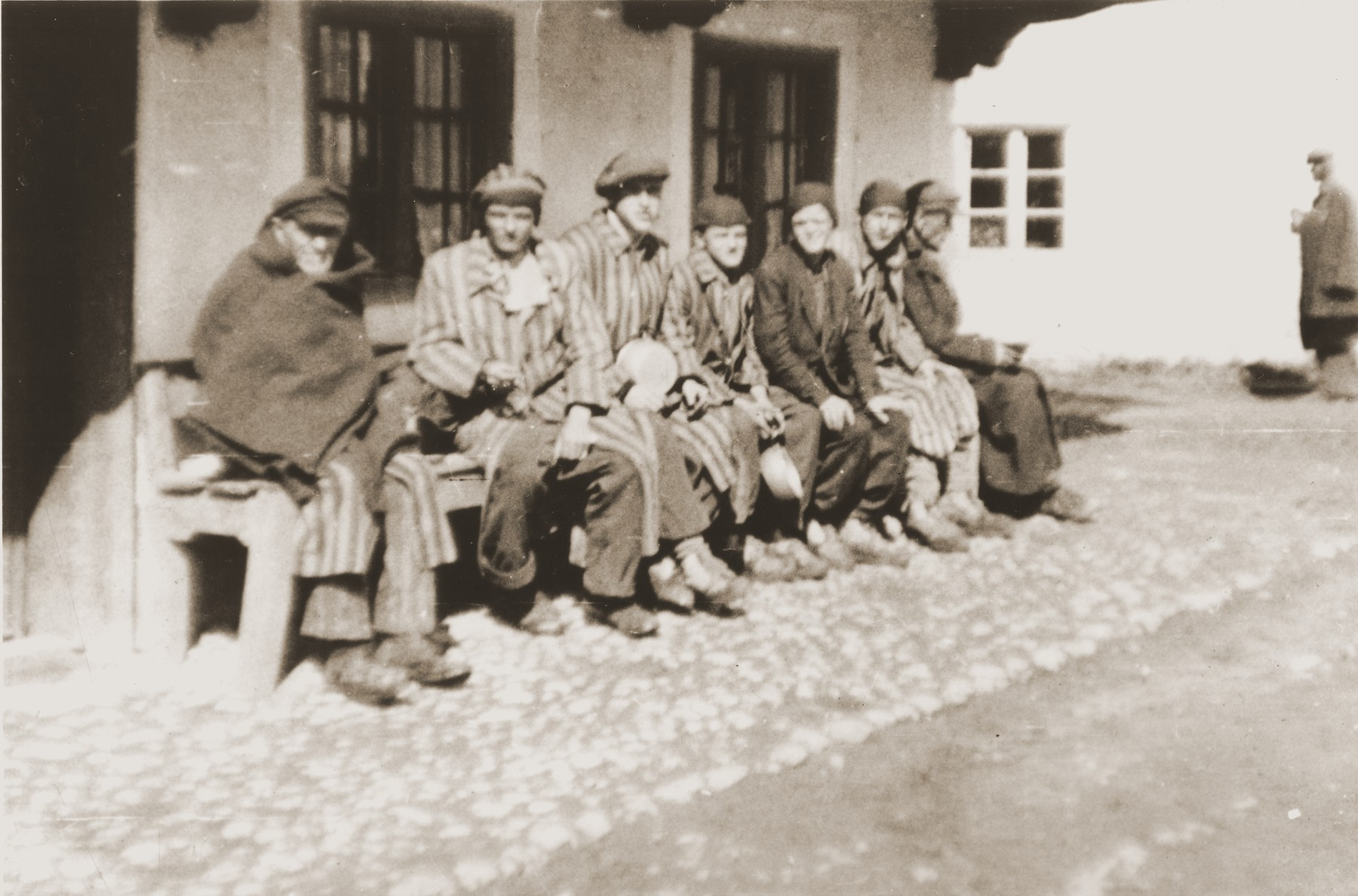 A group of concentration camp prisoners who were liberated on a death march from Dachau, sit on a bench waiting to receive food from Japanese-American soldiers with the 522nd Field Artillery Battalion.