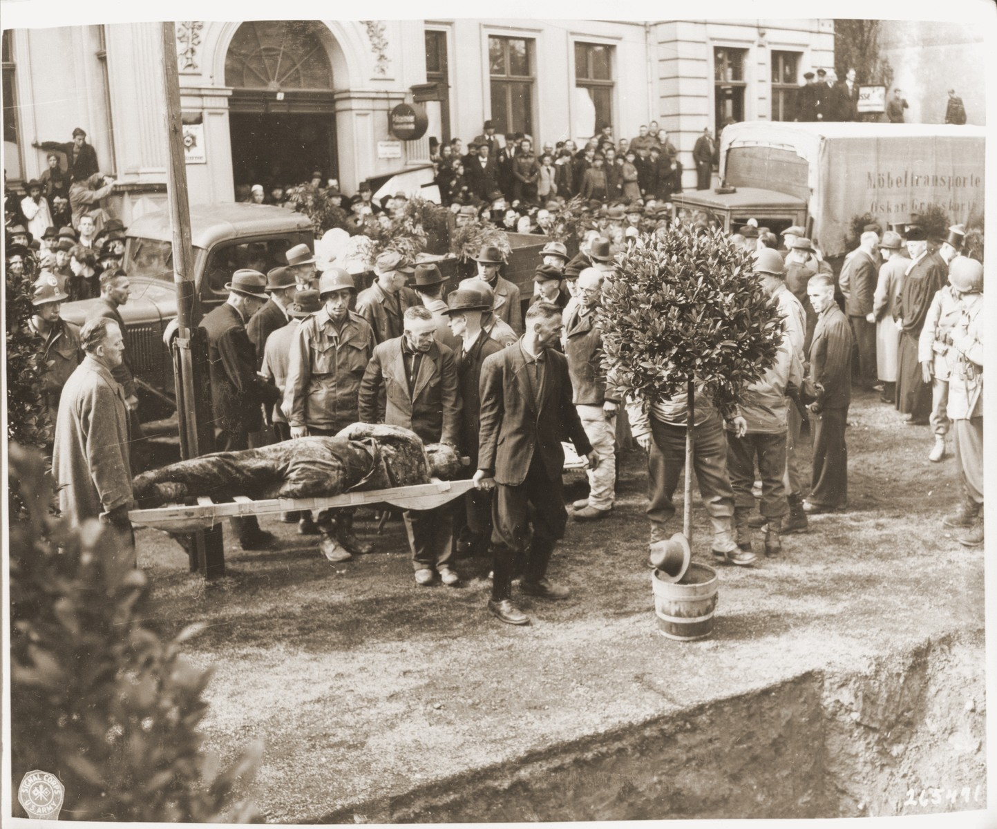 Under the supervision of American soldiers, German civilians bury the bodies of 71 political prisoners, exhumed from a mass grave near Solingen-Ohligs, in front of the city hall.  The victims, most of whom were taken from Luettringhausen prison, were shot and buried by the Gestapo following orders to eliminate all Reich enemies just before the end of the war.