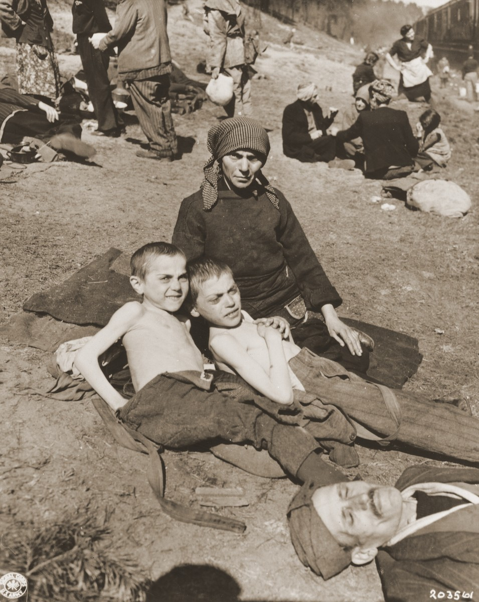 A woman and two children rest next to a stopped train.
