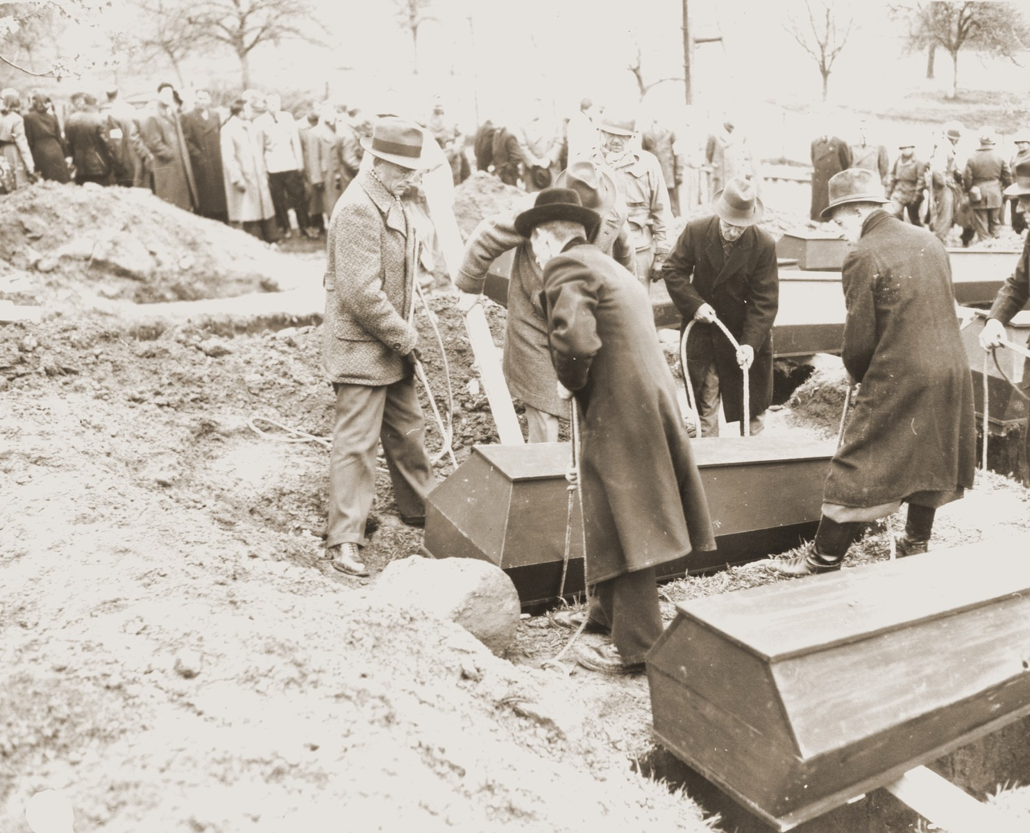 Under the direction of American soldiers, German civilians from Wilhelmshoehe lower a coffin into a grave.  The victim was one of many Italians shot and buried in a mass grave by the Gestapo on March 31, 1945.