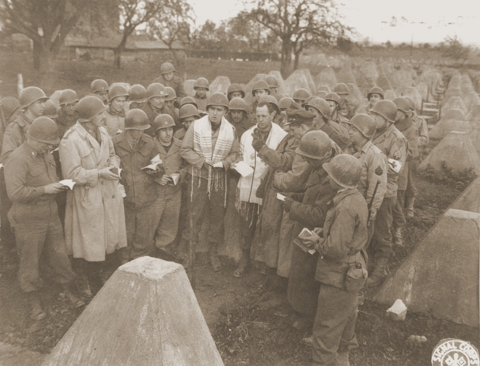 "Mac Fuchs, New York City Cantor, sings as Rabbi Sydney Lefkowitz, Richmond, Va., conducts the first Jewish services from Germany.    James Cassidy of NBC holds the microphone over which the services were broadcast to the U.S.  The services were held in the middle of the concrete ""Dragon-Teeth"" Tank Barriers of the Siegried Line."