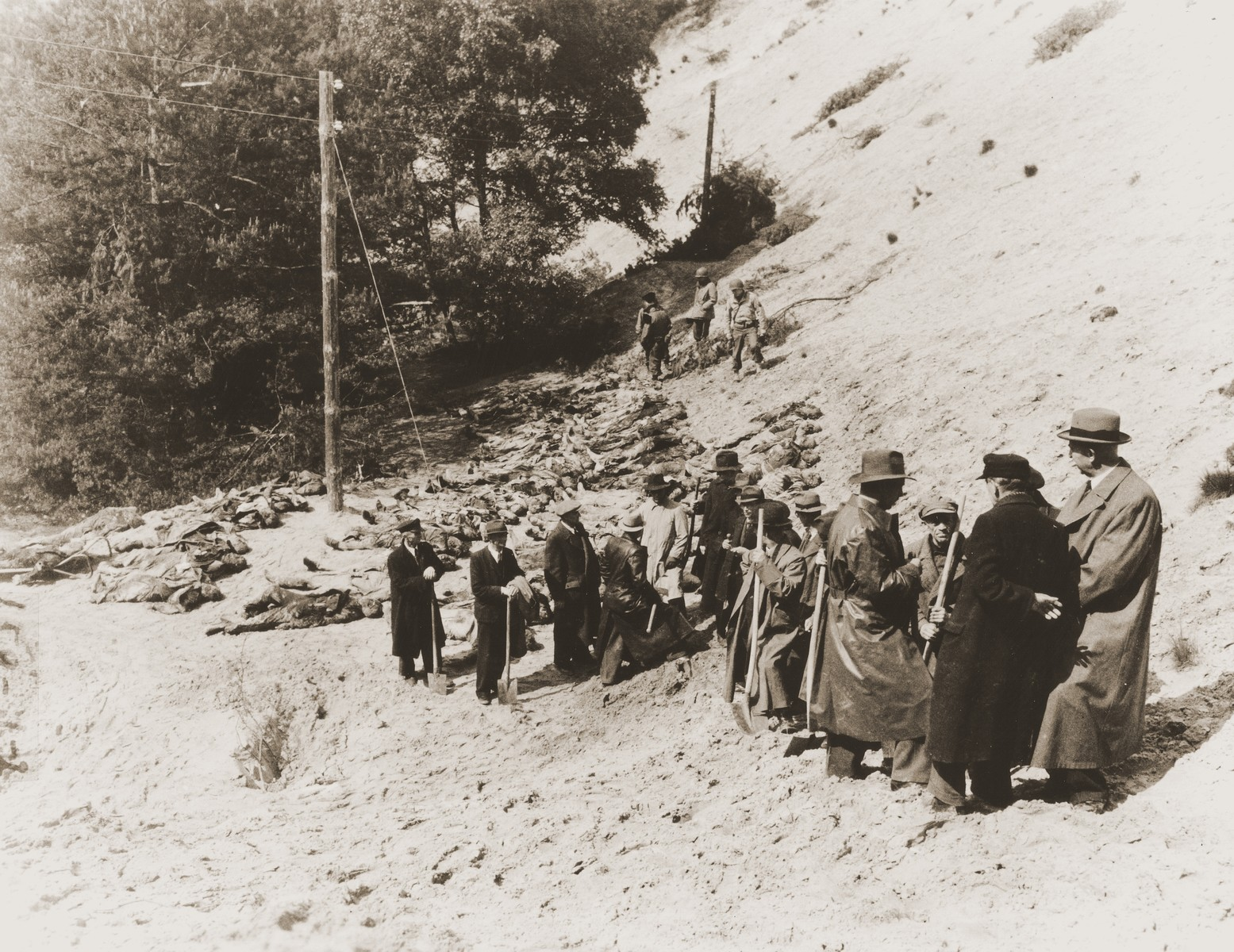 Under the supervision of American soldiers, German civilians leave the site where they exhumed the bodies of 71 political prisoners from a mass grave on Wenzelnberg near Solingen-Ohligs.    The victims, most of whom were taken from Luettringhausen prison, were shot and buried by the Gestapo following orders to eliminate all Reich enemies just before the end of the war.