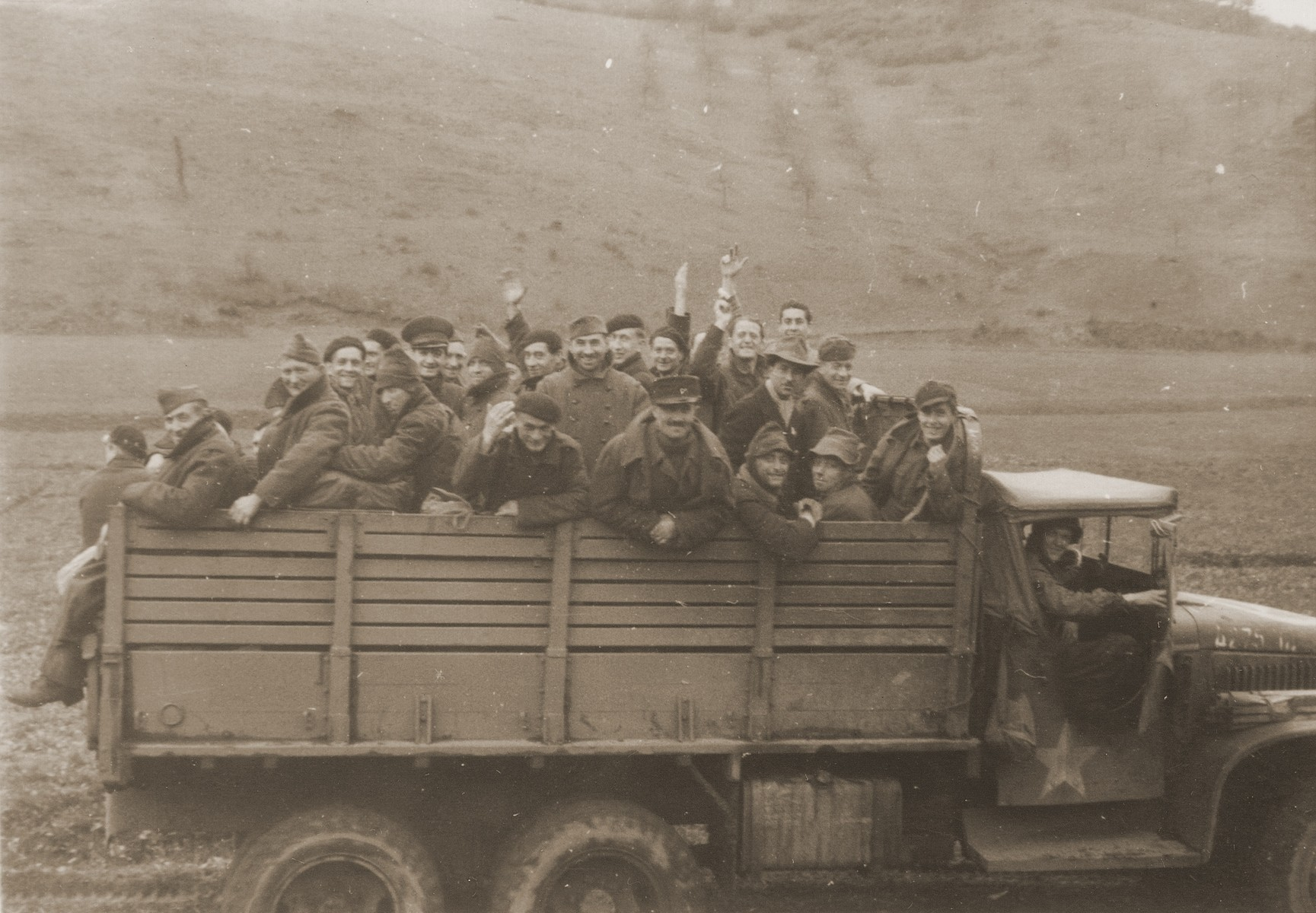 A truckload of displaced persons and concentration camp survivors are transported through the German countryside by American soldiers.
