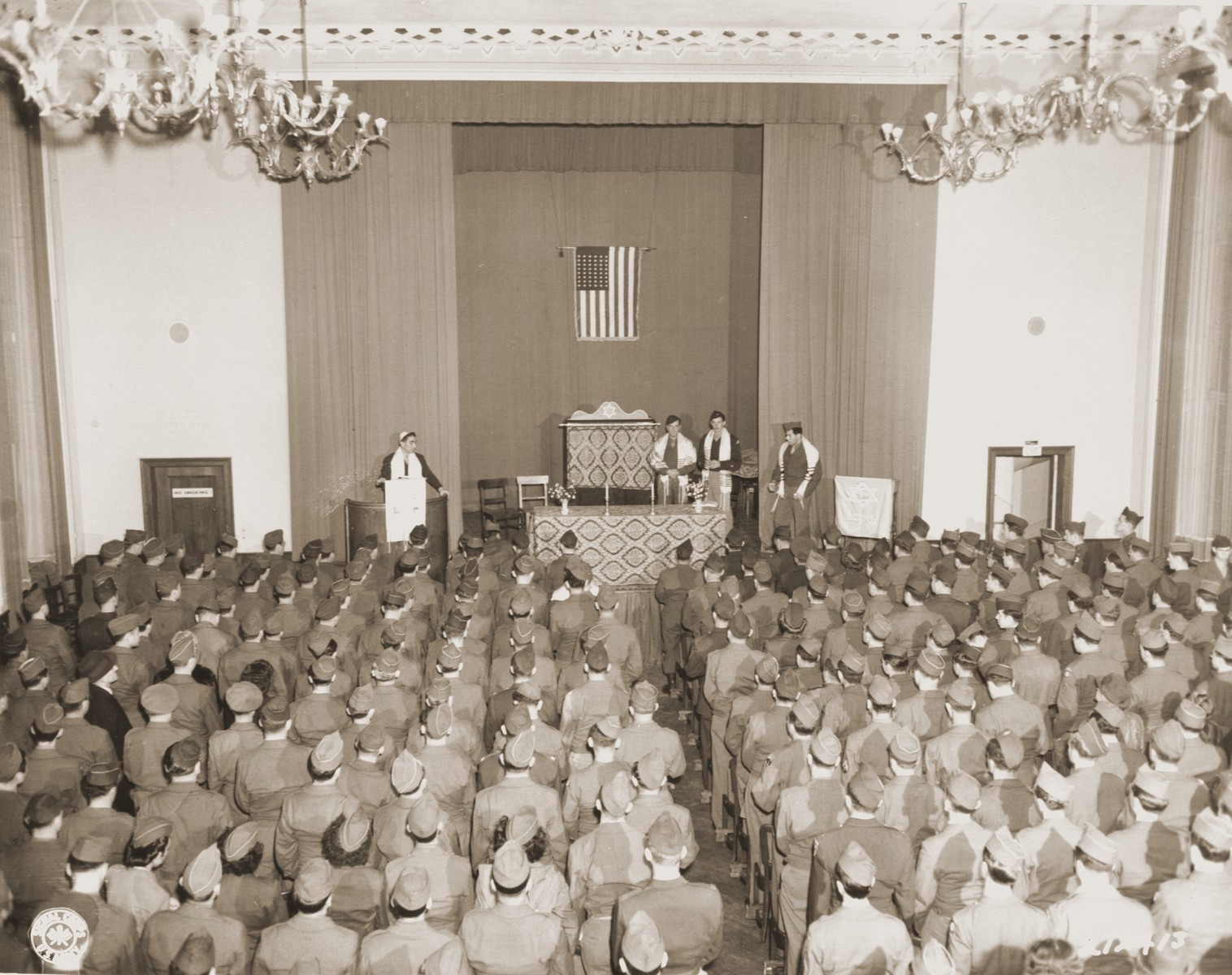 Pfc. Alfred Monheit of the Bronx, NY. receits Kol Nidre at Yom Kippur services held for GI's in Berlin, conducted by chaplain Isadore Breslau, Washington D.C.