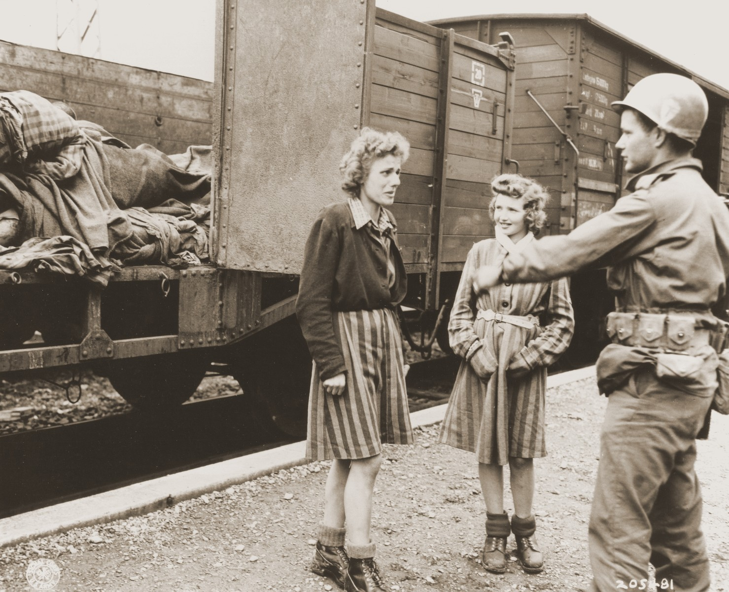 Pfc. Andrew E. Dubill speaks with two Jewish girls who were held prisoner by the SS.    The railroad cars in the background contain the bodies of prisoners who died while on an evacuation transport presumably headed for Dachau concentration camp.