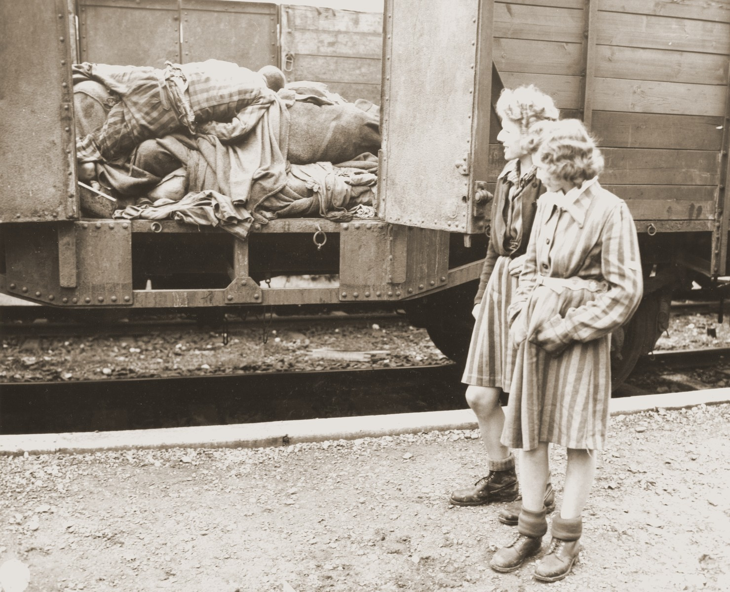 Two Jewish girls stand before a train car laden with the bodies of prisoners who died while on an evacuation transport presumably headed for Dachau concentration camp.