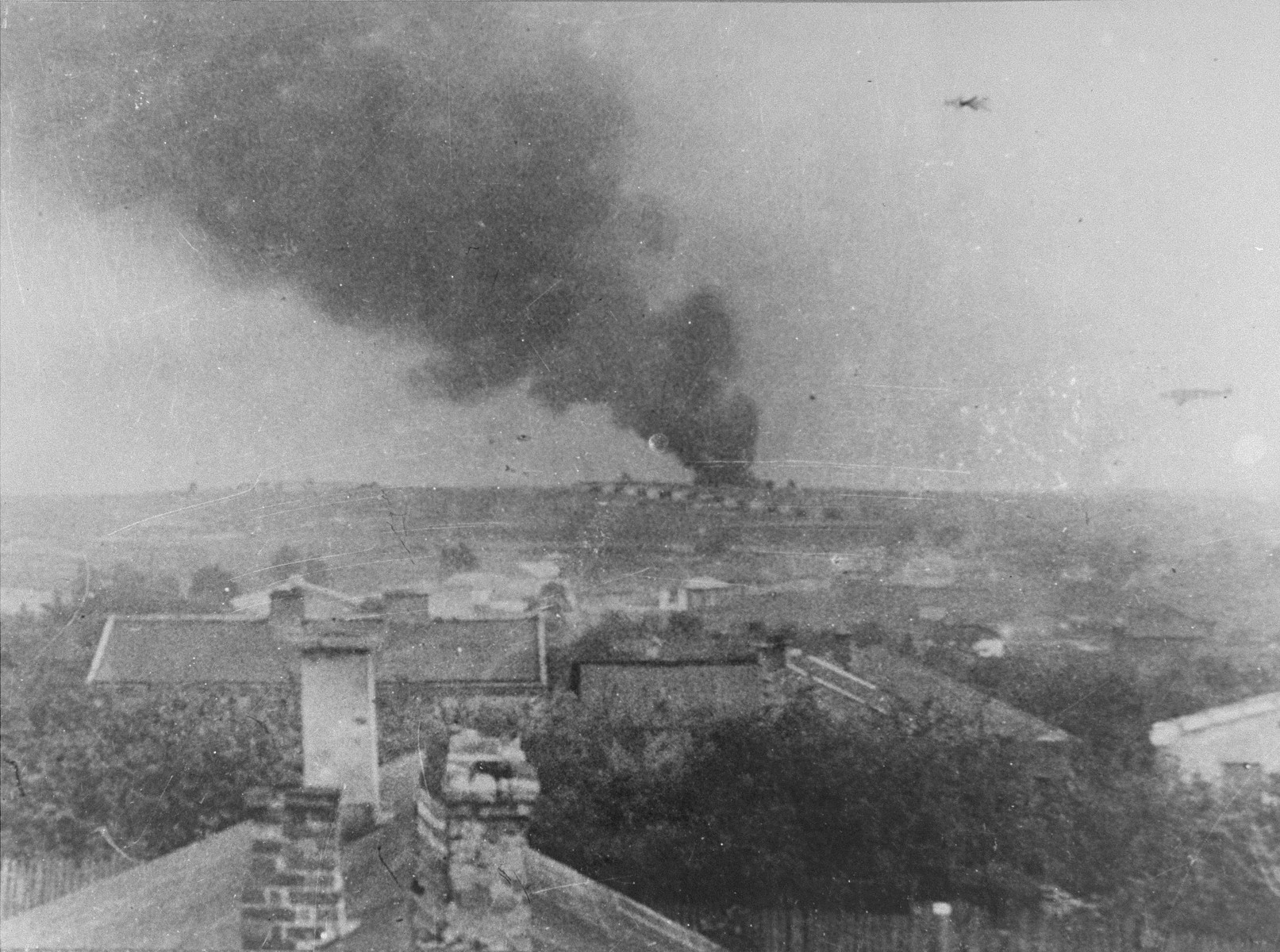 "Majdanek concentration camp, a view from the village ""Dziesiata"". In the background - smoke from a burning pyre of corpses."