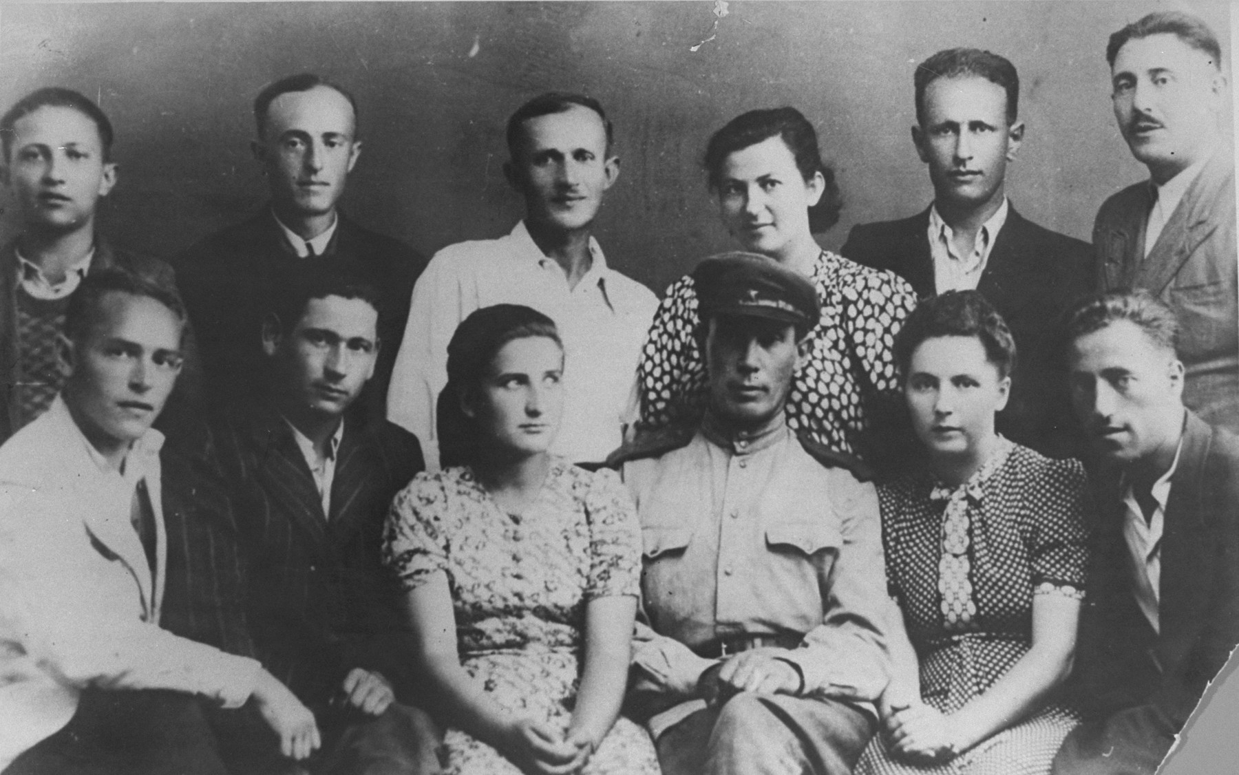 Group portrait of participants in the uprising in the Sobibor death camp.   Among those pictured in the front row are Yosef Ertman (second from the left), Zelda Kelberman (third from left), Esther Raab (second from the right),  The person on the far right has been identified both as Chaim Povroznik and Yehuda Lerner.  [The In the back row are Meyer Zis (far left), Israel Trager (third from the left), and Leib Felhendler (far right).   In the summer of 1943 Jewish prisoners in Sobibor organised an underground group under the leadership of Leon Feldhendler, the former chairman of the Jewish Council in Zolkiew, in the hopes of staging an uprising and mass escape from the camp.  When a group of Soviet Jewish POWs arrived at the camp in mid-September, one of their number, Lt. Aleksandr Pechersky was recruited by the underground and put in charge of the operation, with Feldhendler as his deputy.  The uprising broke out on October 14, 1943, during which eleven SS guards were killed and three hundred prisoners escaped.  All but approximately fifty were apprehended and killed.
