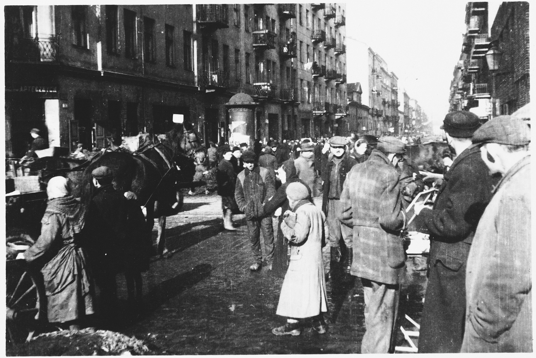 Jews move along a crowded street in the Warsaw ghetto.