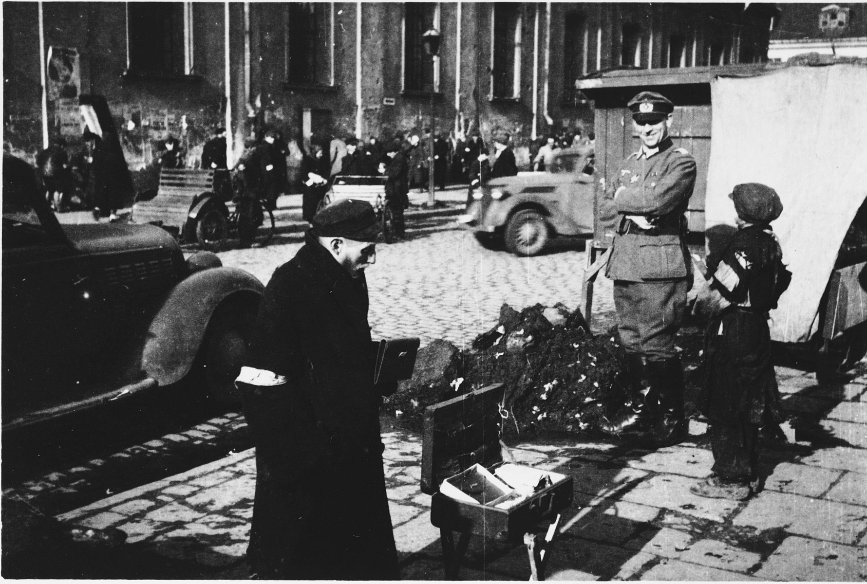 A Jew wearing an armband stands near a makeshift vending stand on a street in the Warsaw ghetto.  A German officer (top right) views the scene.