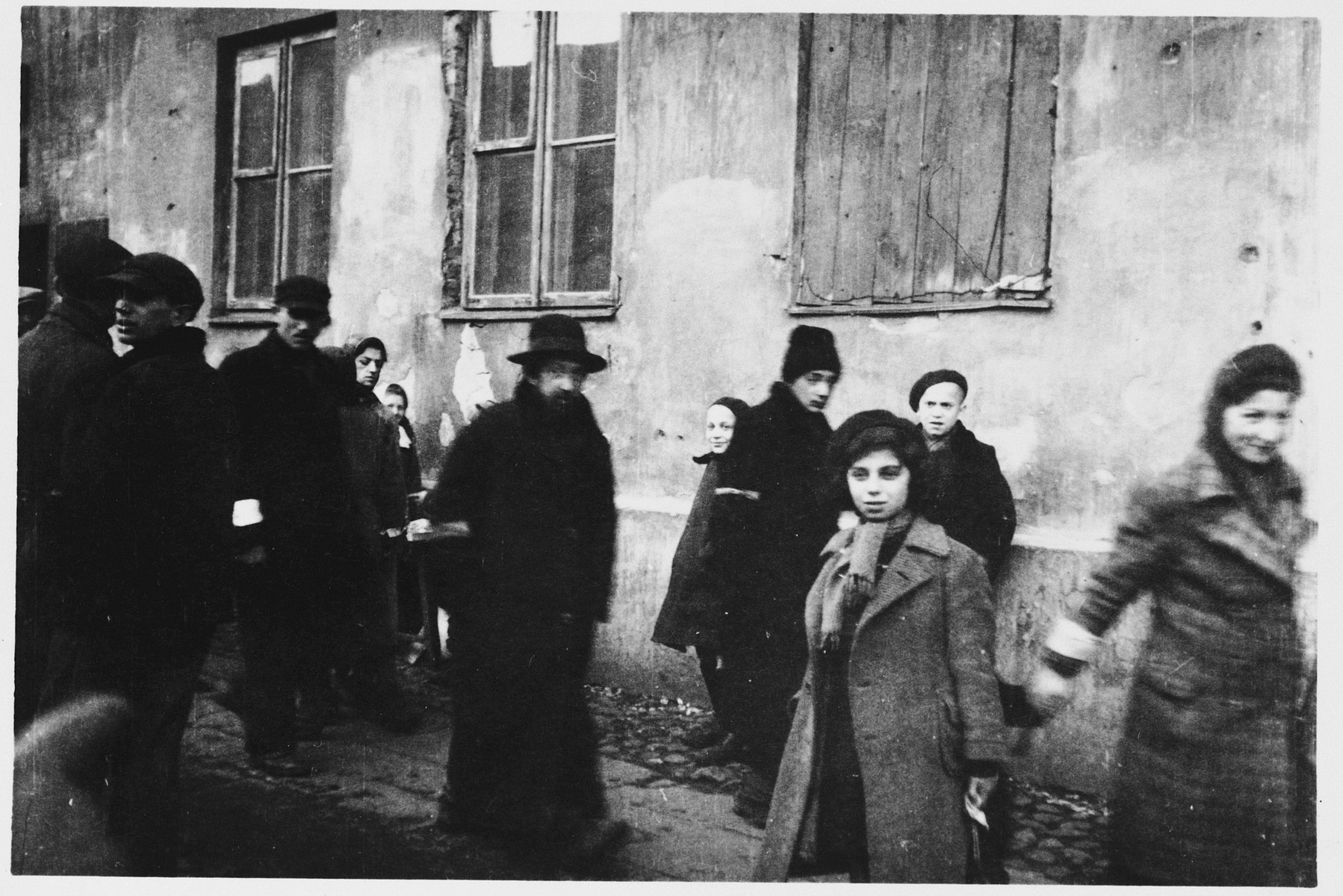 Jews wearing armbands are gathered outside a partially boarded-up building in the Warsaw ghetto.